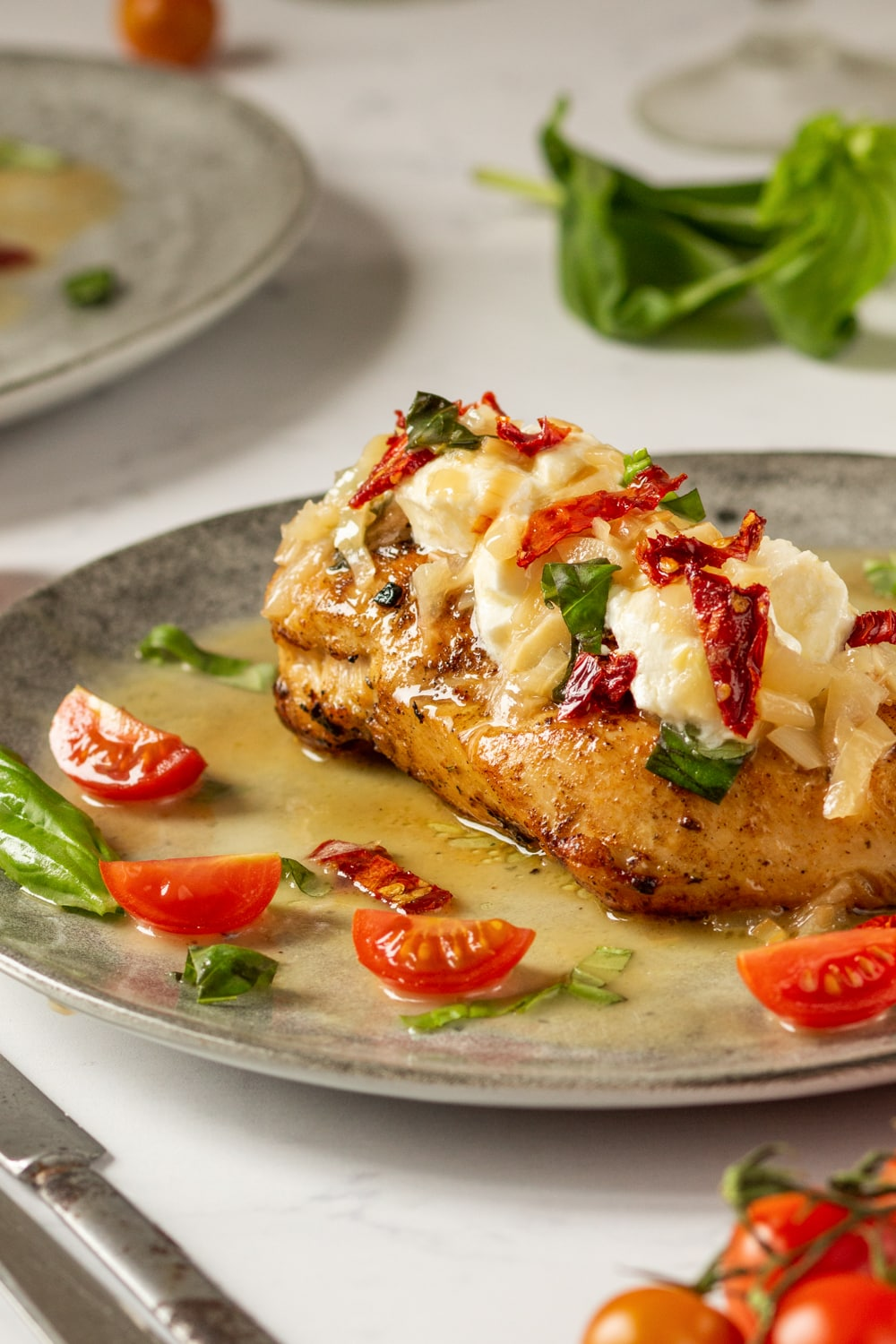 A chicken breast on a plate, and the chicken is topped with butter, goat cheese, sun-dried tomatoes, and goat cheese.