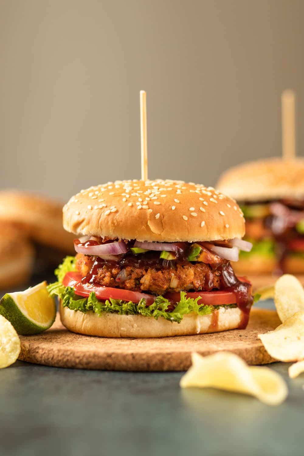 A shrimp burger with a wooden sandwich pick holding it together. The burger has onions, lettuce, tomato, and barbecue sauce on it.