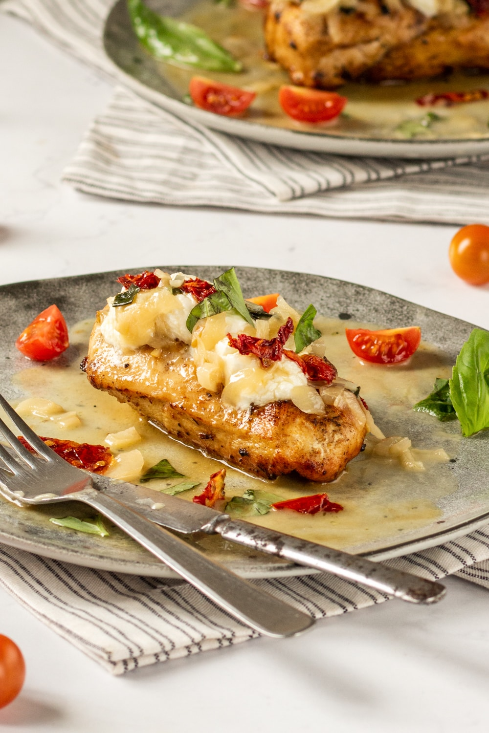 A chicken breast on a grey plate. There is a fork and a knife next to the chicken, and the chicken is topped with cheese, sun-dried tomatoes, and basil.