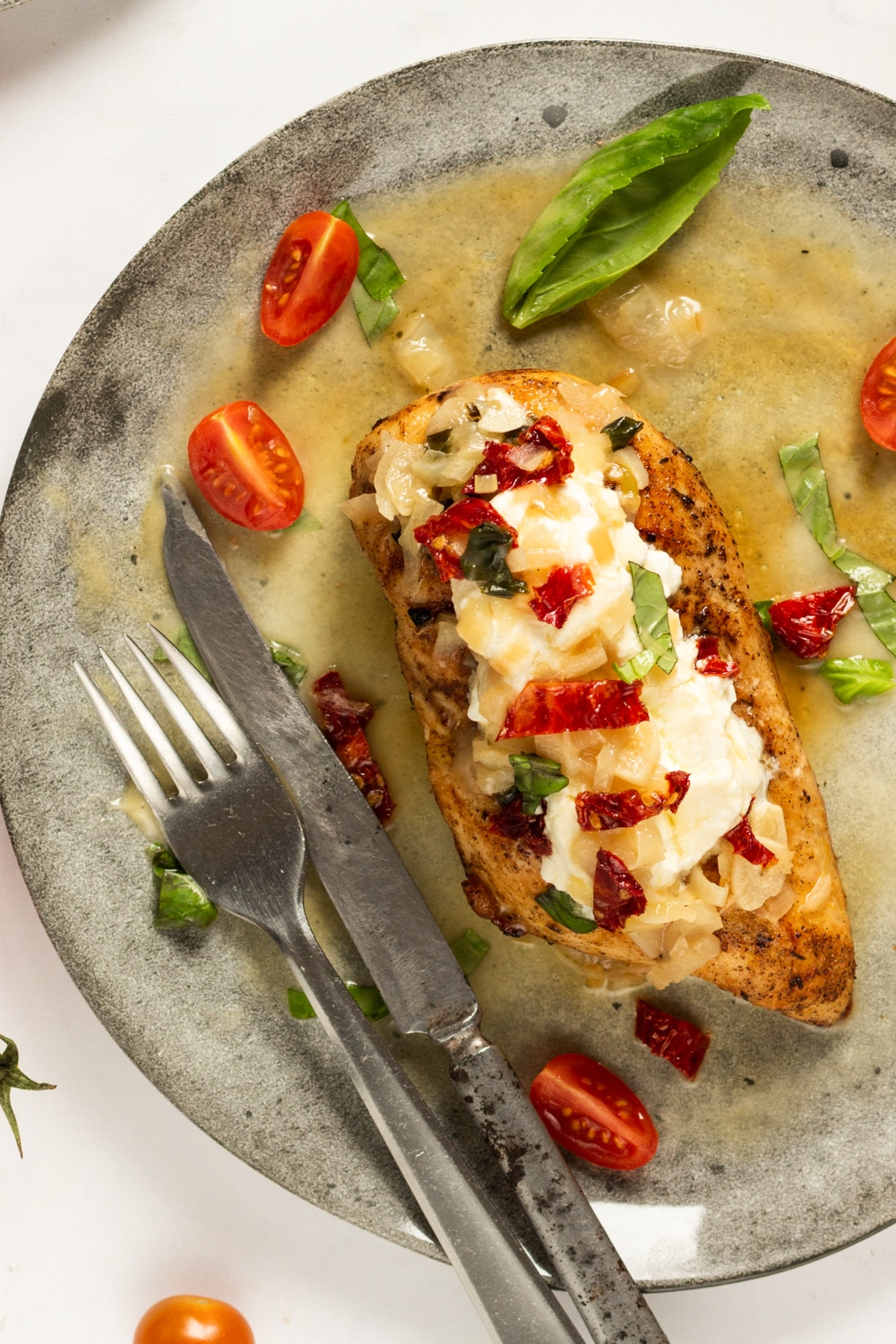 AA chicken breast on a grey plate. There is a fork and a knife next to the chicken breast. The top of the chicken has cheese, sun-dried tomatoes, and basil on it.