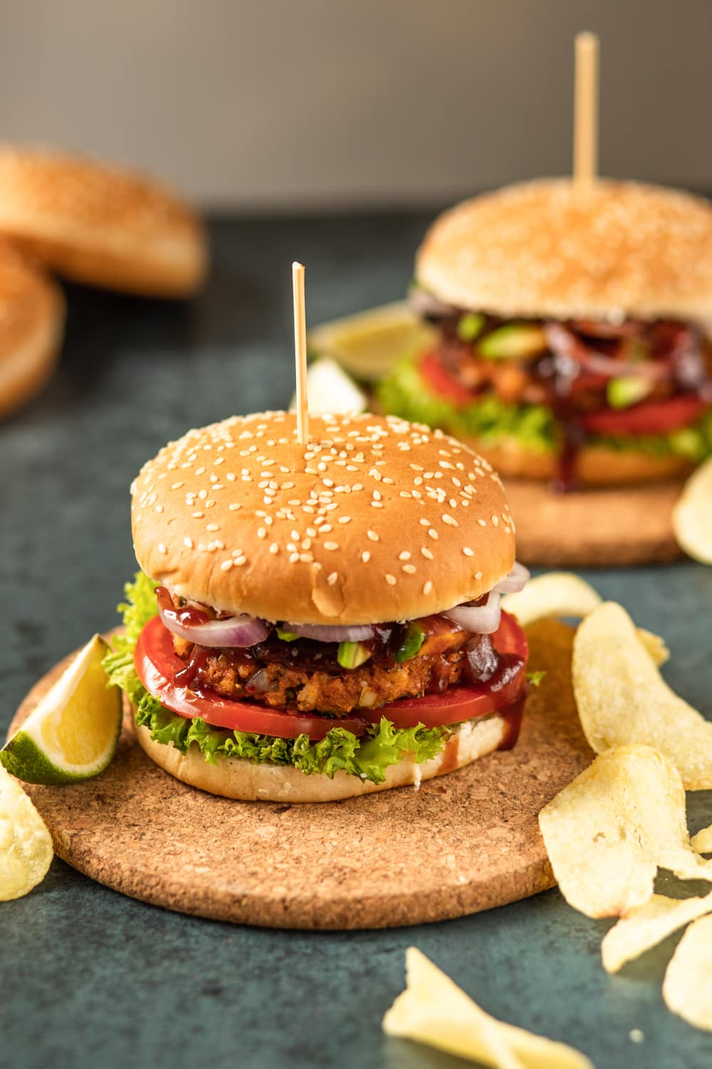 Shrimp burgers with lettuce, tomato, onions, and barbecue sauce. The burgers have sesame seed buns, and are set on cork plates.