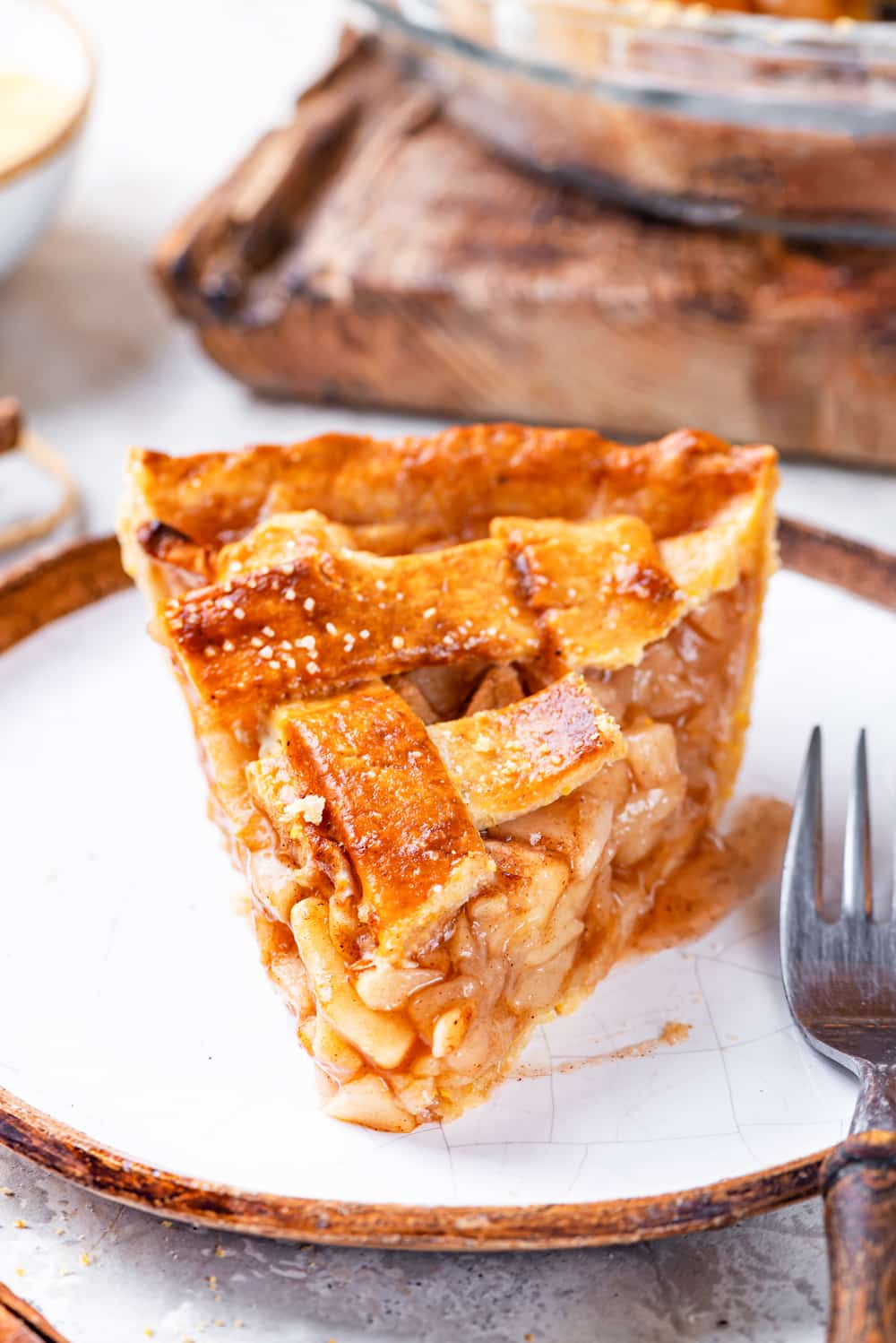 A slice of vegan apple pie on a white plate with the tip of the pie at the front and crust at the back. There is a fork on the right side of the plate and the plate is on a grey counter.