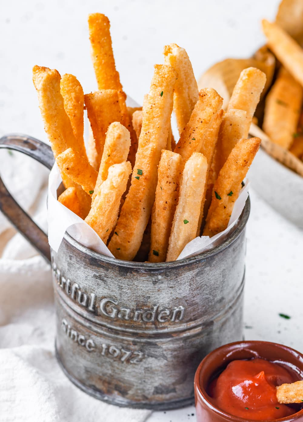 A metal cup filled with keto french fries standing upright on top of a piece of parchment paper. There is a small cup of ketchup in front of the metal cup with a fry in it. The metal cup is half on a white tablecloth and half on a white table. The ketchup is on the table.