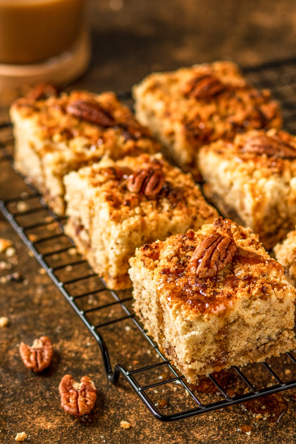 Three pieces of gluten free coffee cake in a row with two pieces to the side in a blurred view. There is one pecan on each piece of coffee cake and the coffee cake is on a wire rack on top of stone.