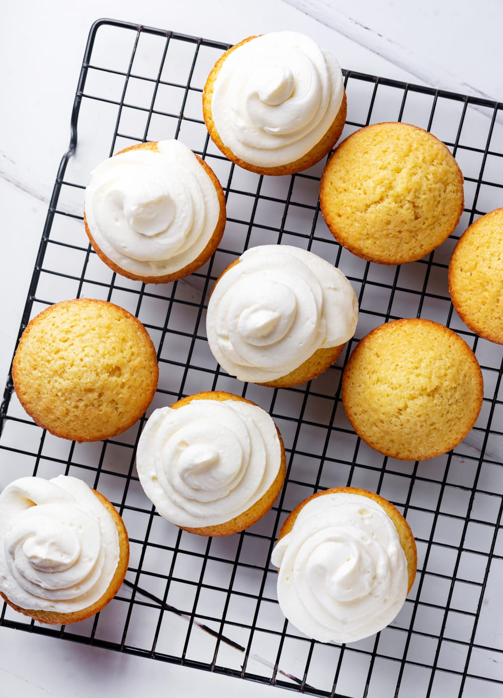 An overhead view of three unfrosted keto vanilla cupcakes and six cream cheese frosted keto vanilla cupcakes. The cupcakes are on a wire rack which is on white counter.