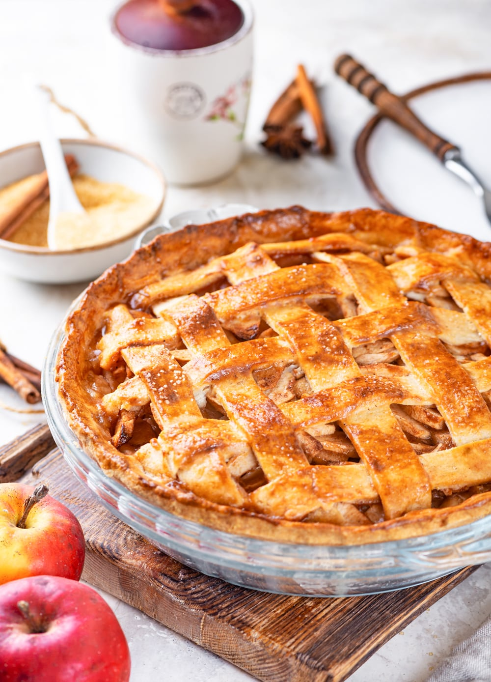 A vegan apple pie in a glass pie dish. The pie dish is on a wooden cutting board which is on a grey counter. There is a bowl of sliced apples and a cup of coffee behind the pie and two whole apples in front of the pie to the left of the cutting board.