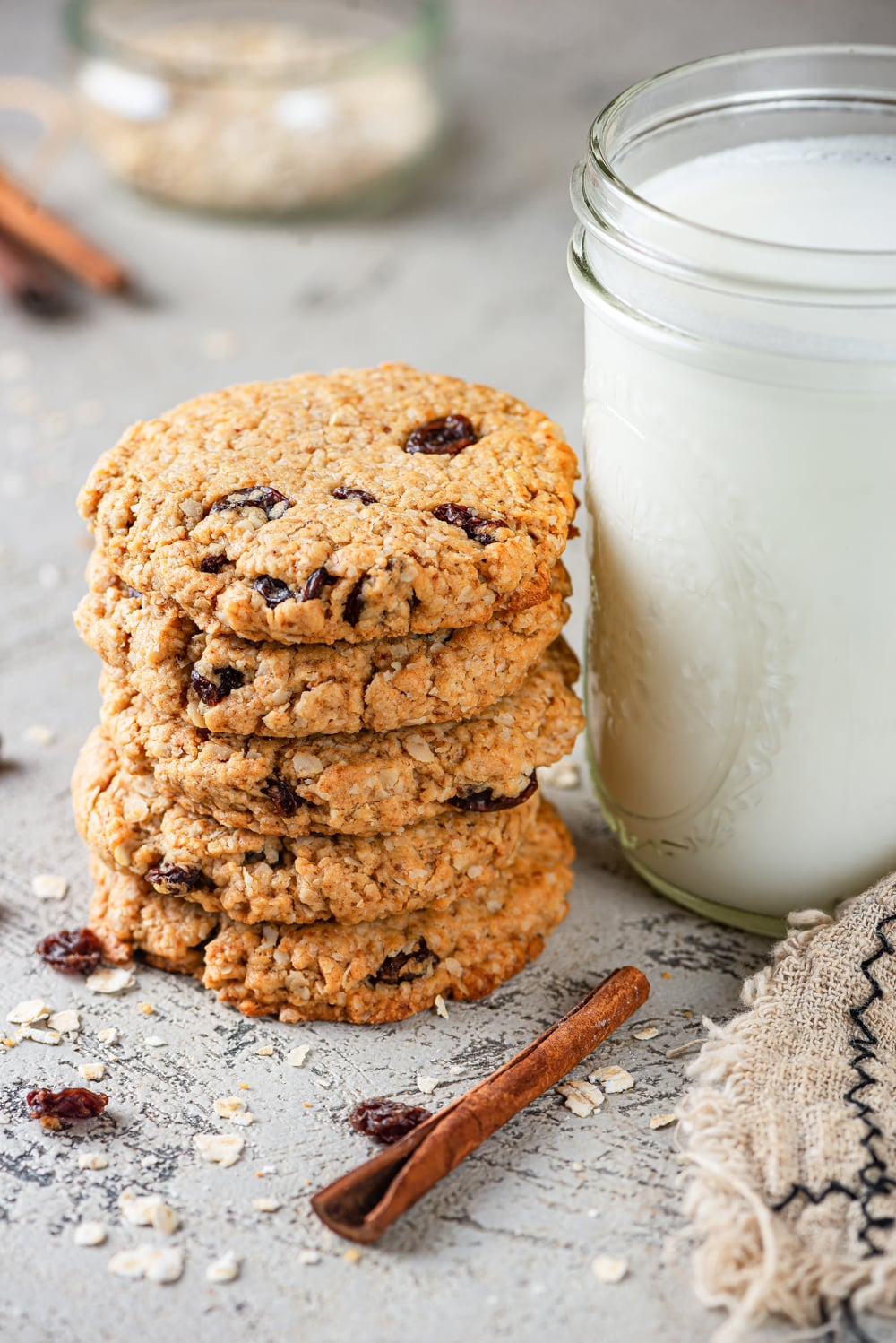 A stack of five vegan oatmeal raisin cookies with a tall glass jar of milk next to it on the right. There is a cinnamon stick in front of the cookies and milk with a few oats around them. Everything is on a grey counter.