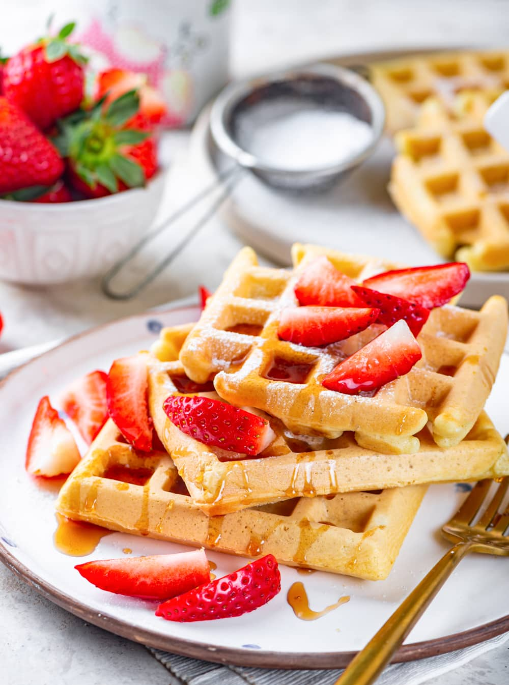A white plate with three square vegan waffles unevenly stacked on top of each other. Maple syrup is drizzled on top and there are cut up strawberries on the waffles with a gold fork to the right of the waffles. A white plate with two plain vegan waffles are behind the plate and there is a bowl of strawberries to the left of it.