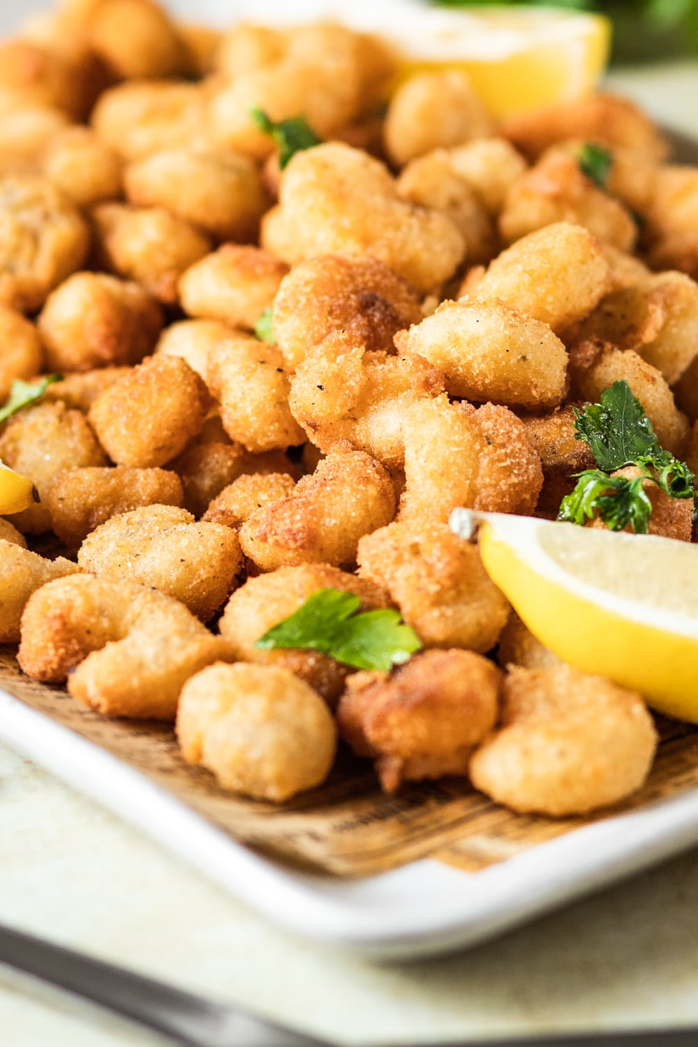 A zoomed in view of popcorn shrimp filling the surface of a white square plate with brown newspaper on the plate.