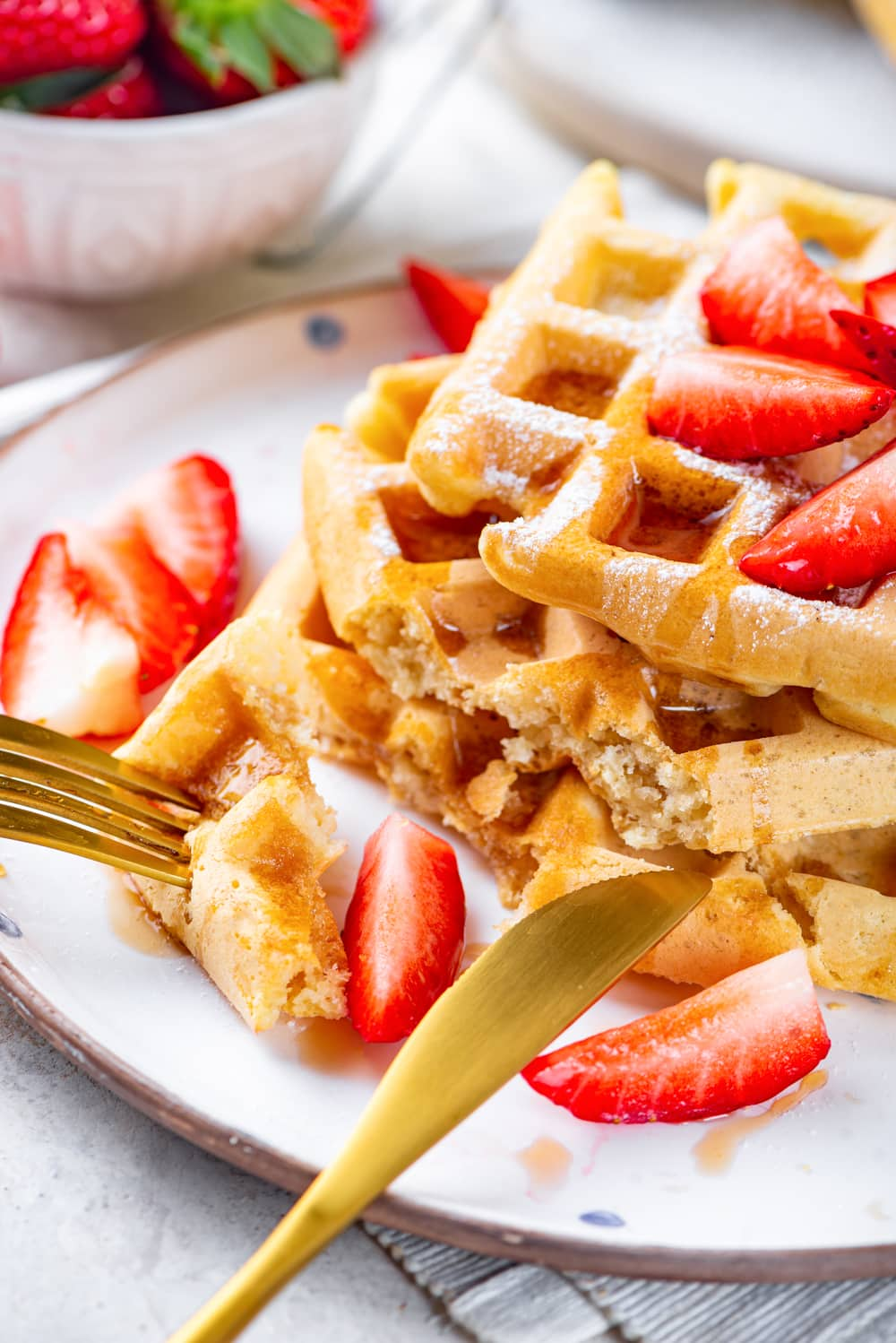 A white plate with three square vegan waffles stacked on top of each other with maple syrup and cut strawberries on them. A gold fork is stabbed into a cut piece of waffle with a gold knife laying on the bottom waffle. The plate is on a white table.