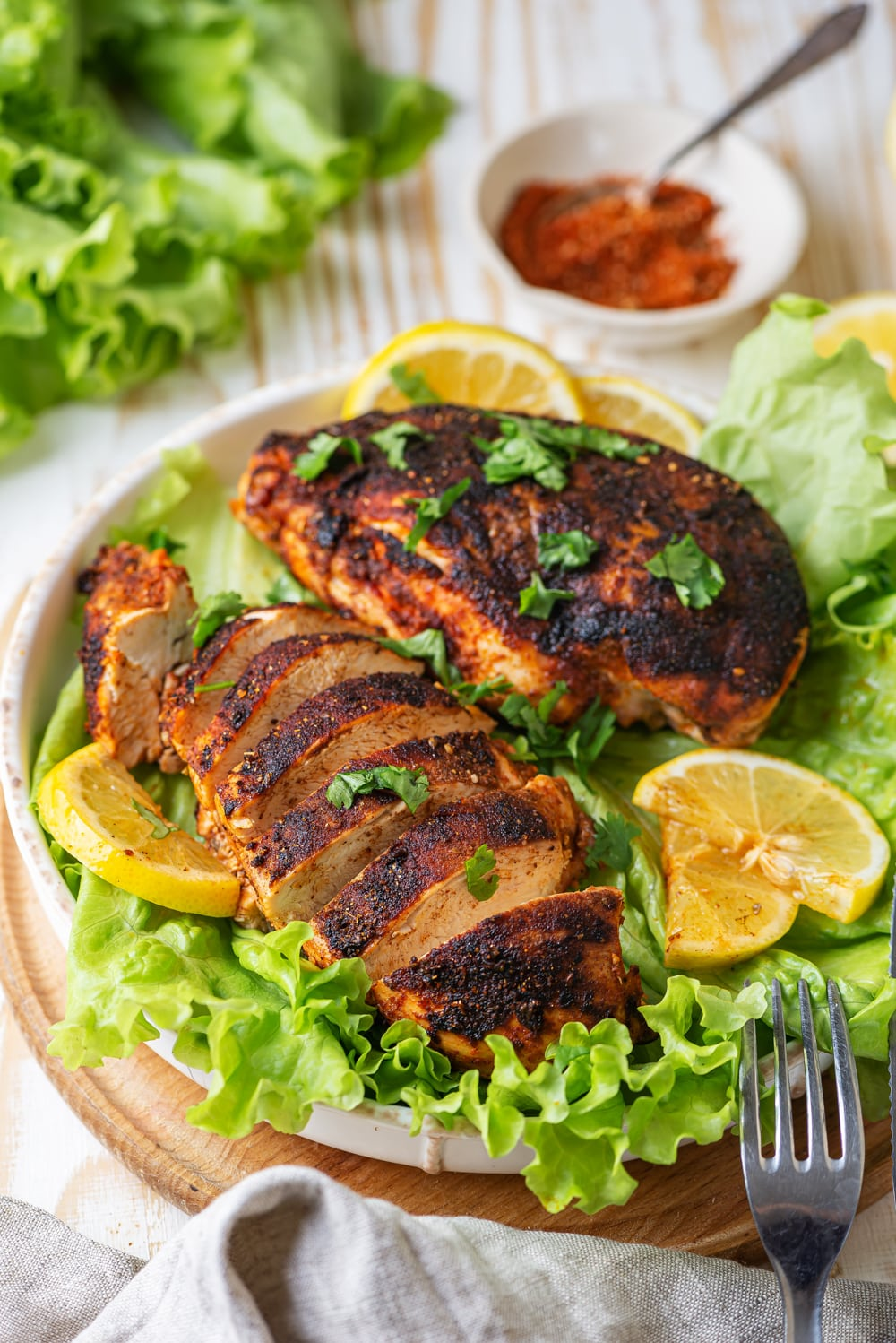 A white plate of one whole piece of blackened chicken and one sliced piece of blackened chicken set on top of leafy green lettuce. There are a few lemon slices on the plate with a fork at the edge of the bottom of the plate. A small white bowl of seasonings is behind the plate.