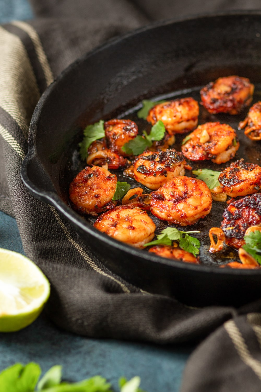 Several pieces of blackened shrimp in a skillet on top of a brown tablecloth. Half of a lime is in front of and to the left of the skillet on a blue counter.