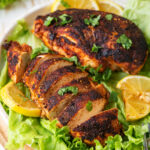 Two pieces of blackened chicken on a white plate with leafy green lettuce underneath the chicken. The piece of chicken at the front of the plate is cut into slices and the other piece of chicken at the back of the plate is whole. There are four slices of lemon on the side and back of the chicken. A white bowl of seasonings is behind the plate of chicken. The plate is on a wooden sauce and everything is on a wood table.