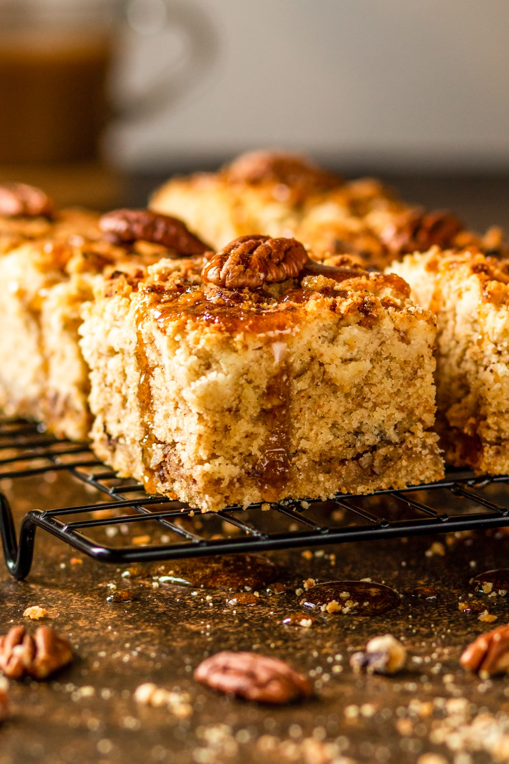 A side view of one piece of coffee cake with several pieces in the background. There is one pecan on top of each piece of coffee cake. The coffee cake is on a wire rack which is sitting on a stone table.