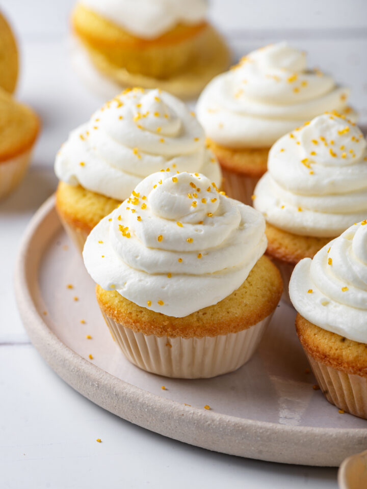 Five keto vanilla cupcakes with keto cream cheese frosting on a grey plate. There is one unwrapped cupcake behind the plate and everything is set on a white counter.