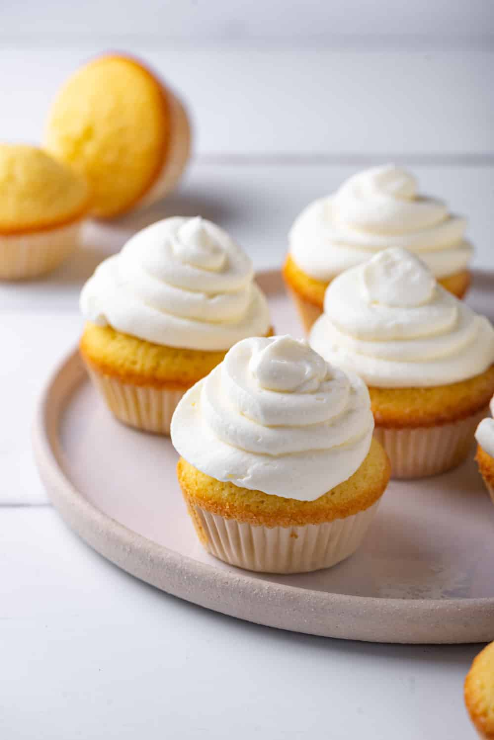 A grey plat with four keto cream cheese frosted vanilla cupcakes on it. There are two unfrosted cupcakes behind the plate. One is upright and one is on its side. Everything is set on a grey counter.