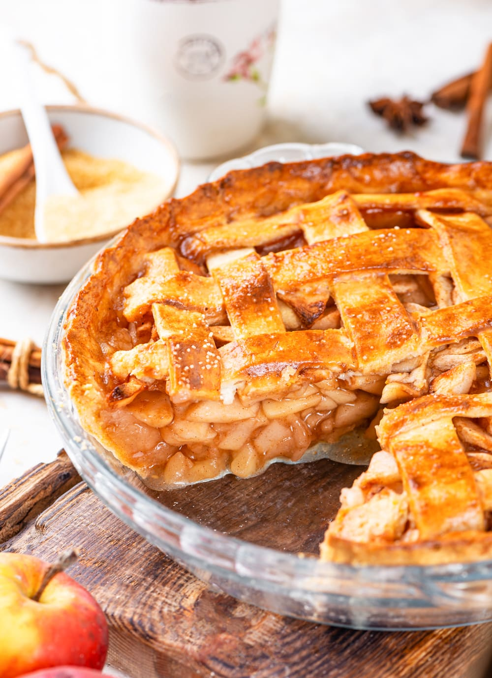 A vegan apple pie in a glass pie dish with one sliced taken out of the pie. The pie dish is on a wooden cutting board with a bowl of sliced apples behind it.