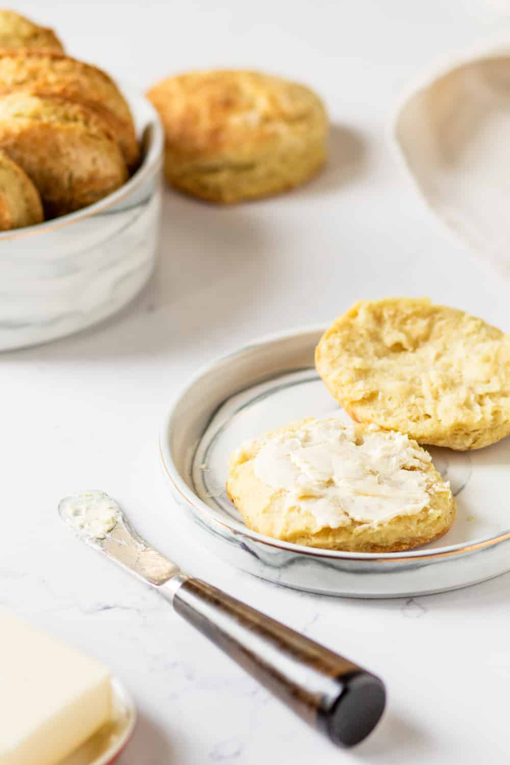 A white plate with a cut open vegan biscuit. The bottom half has a slab of butter on it and is in front of the top half. There is a knife with butter on it in front of the plate and a stick of butter in front of the knife. There is a white bowl filled with vegan biscuits behind plate to the left. A whole vegan biscuit is on the right side of the bowl. Everything is on a white counter.