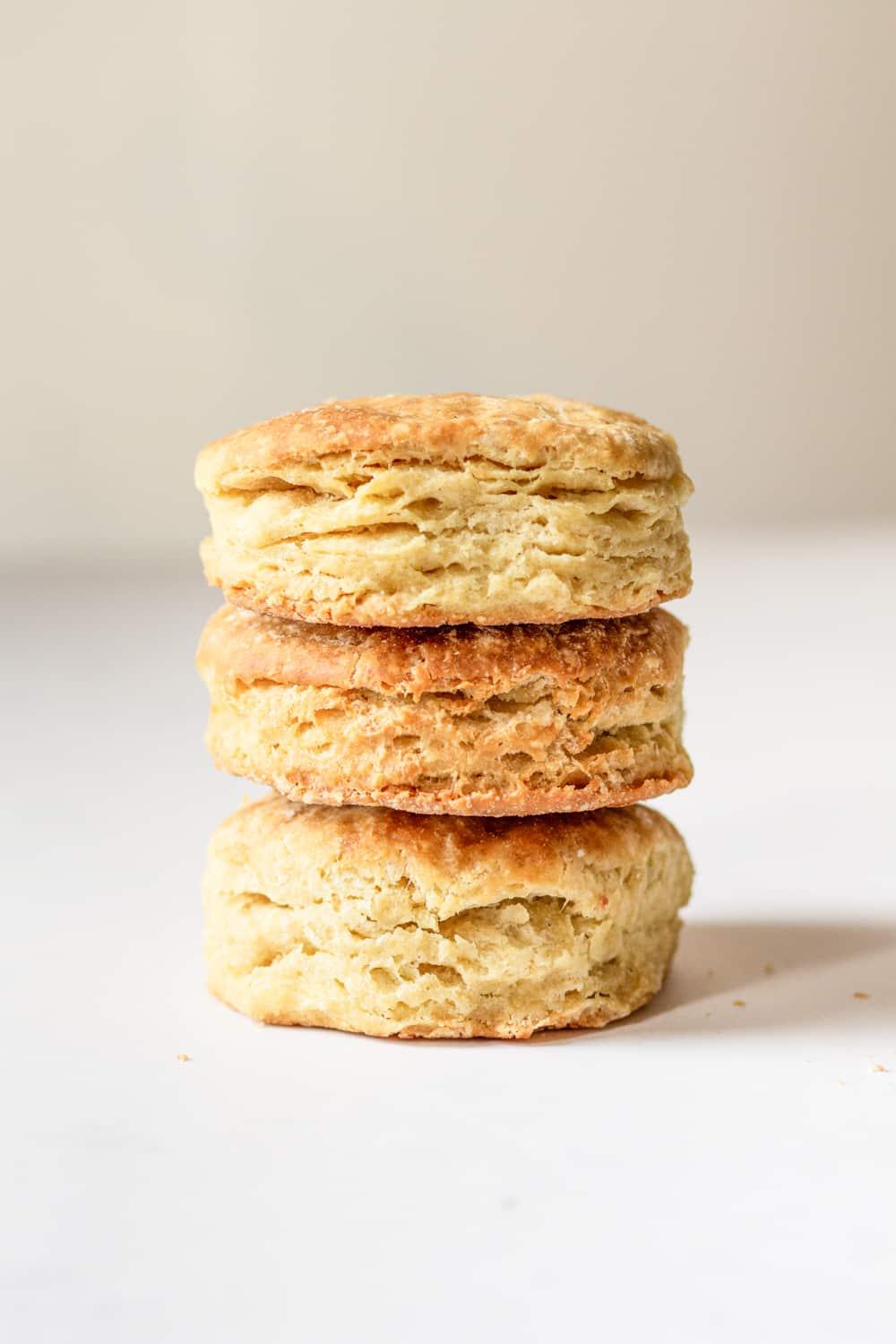 Three vegan biscuits stacked on top of one another. The biscuits are on top of a white counter.