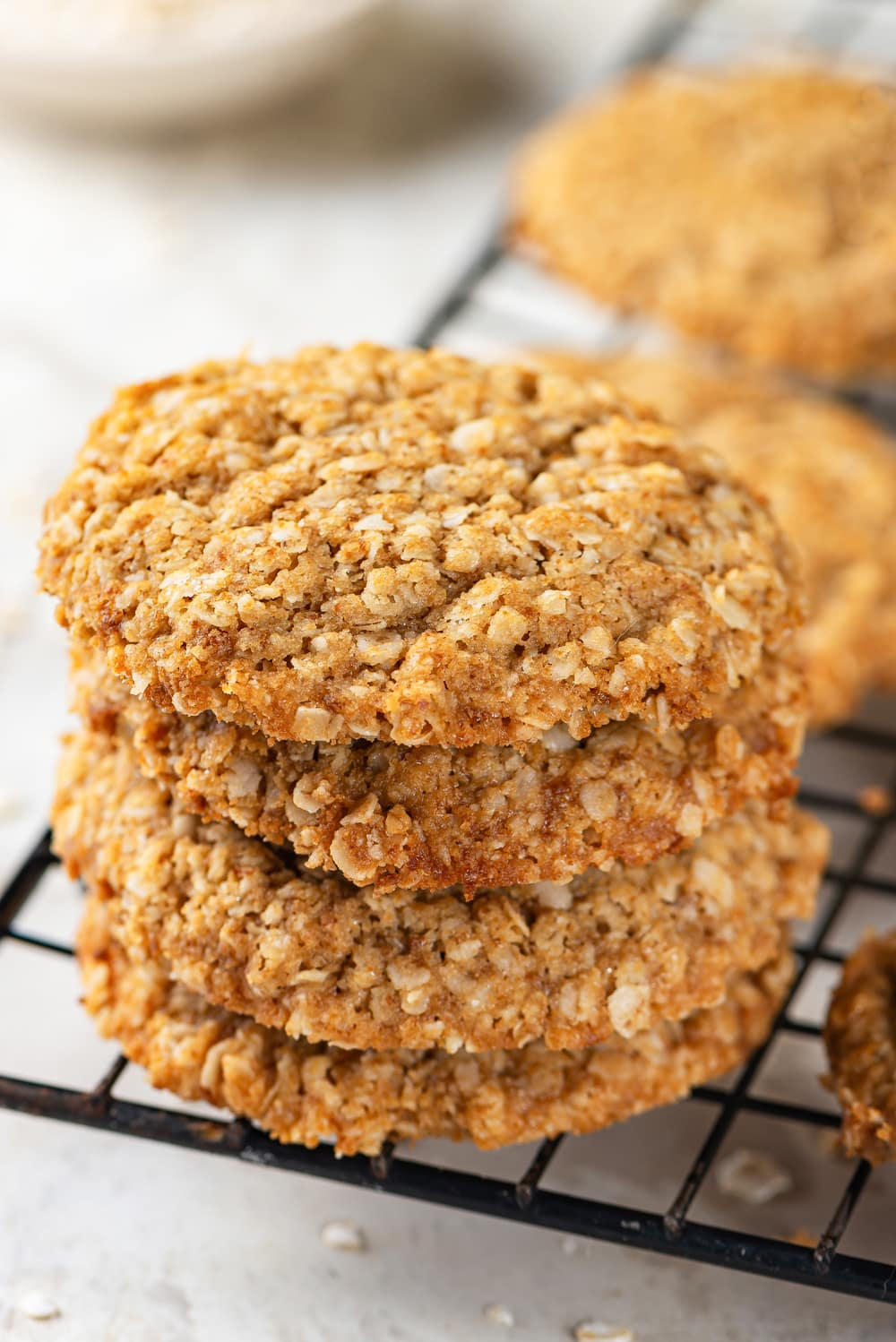 Four vegan oatmeal cookies stacked on top of each other on a black wire rack. There are two oatmeal cookies on the rack behind the stack of cookies. The wire rack is on a white counter.
