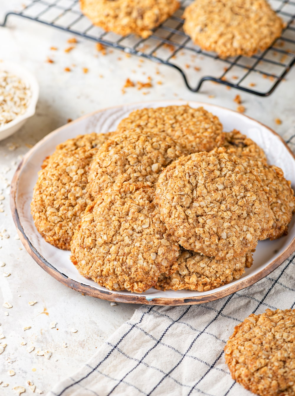 Eight vegan oatmeal cookies overlapping one another on a white plate. There are two oatmeal cookies on a black wire rack behind the plate of cookies. One oatmeal cookie is on a white and black plaid tablecloth in front of the plate of cookies. Everything is on a white counter.