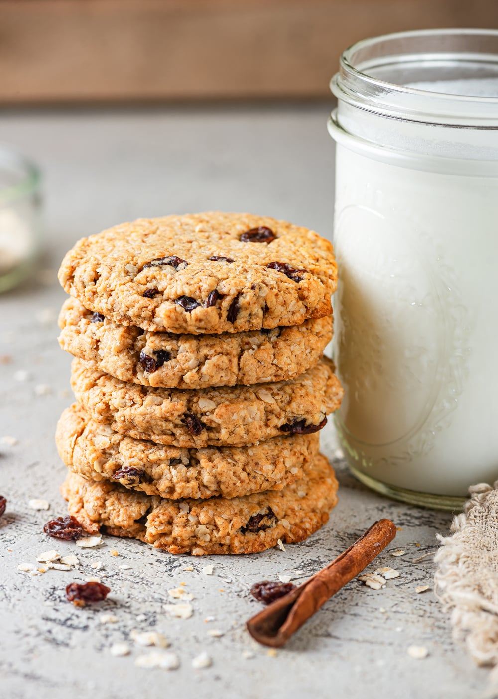 Five vegan oatmeal raisin cookies stacked on top of one another. A tall glass jar of milk is to the right of the cookies. A cinnamon stick is in front of the cookies and milk with a few raisins and oats scattered around them. Everything is on a grey table.