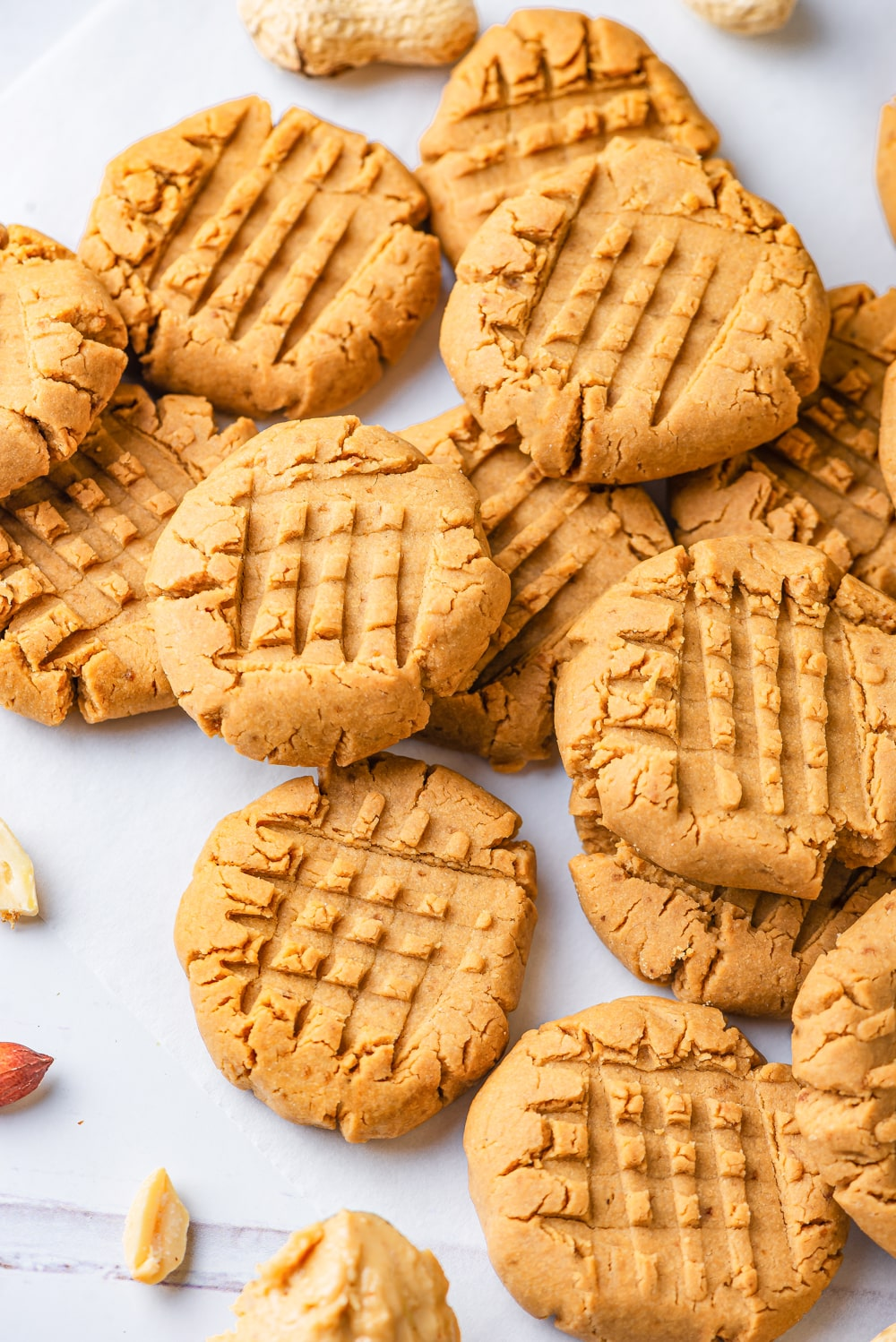 Vegan peanut butter cookies scattered on a white counter with some cookie on top of each other and some overlapping the other cookies,