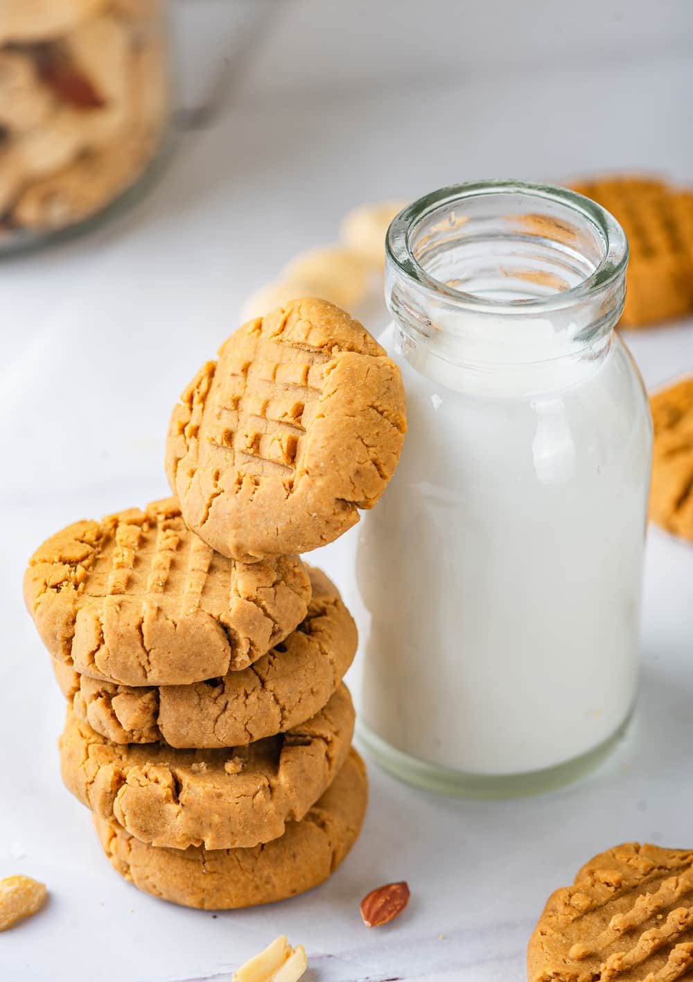 A stack of four vegan peanut butter cookies with a fifth cookie on its side leaning against a tall glass jar of milk. The glass jar of milk is to the right of the stack of cookies. Everything is on top of a white counter.