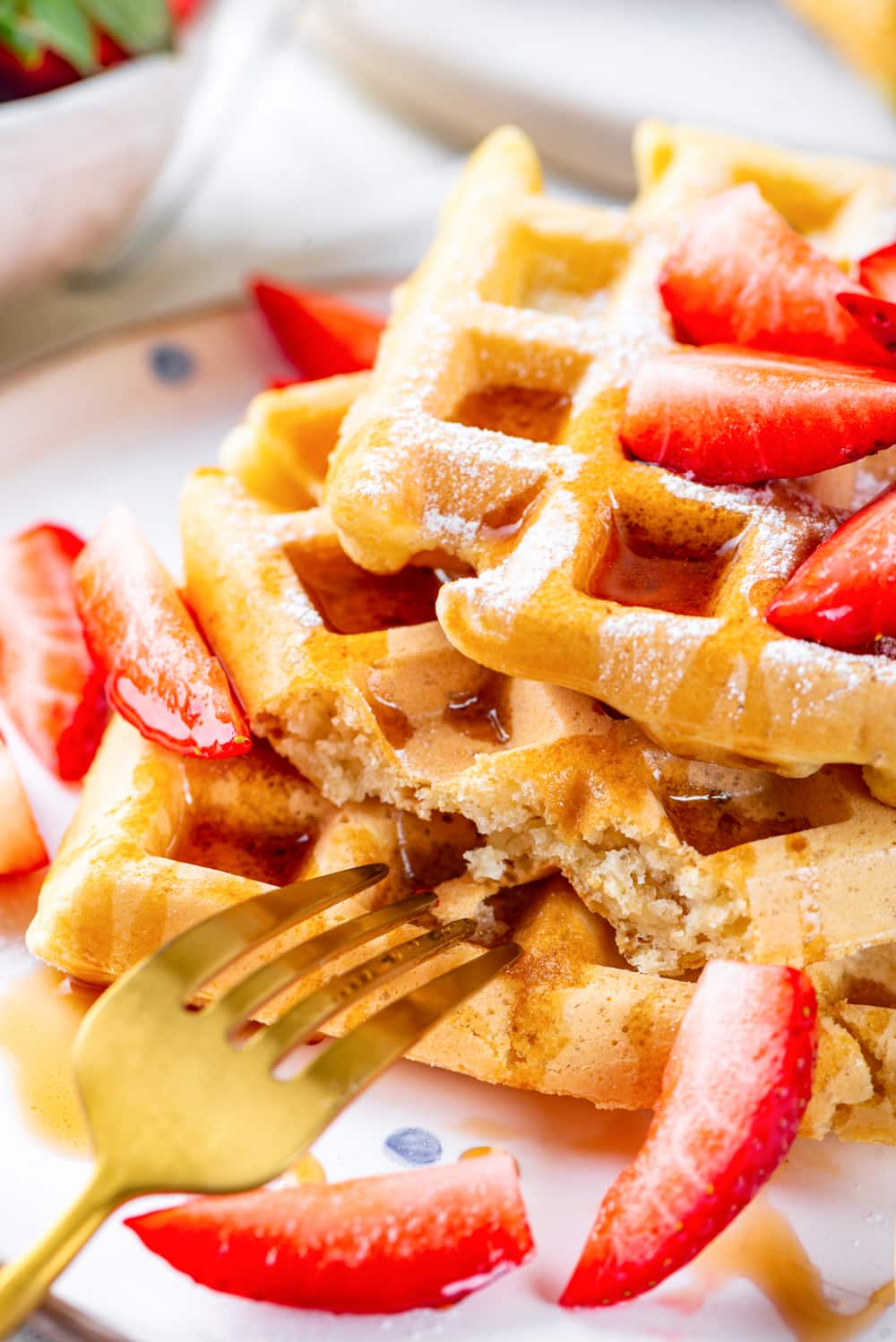 An uneven stack of three square vegan waffles with a piece cut out of the middle waffle. A gold fork is leaning against the bottom waffle and cut up strawberries and maple syrup is on the waffles.