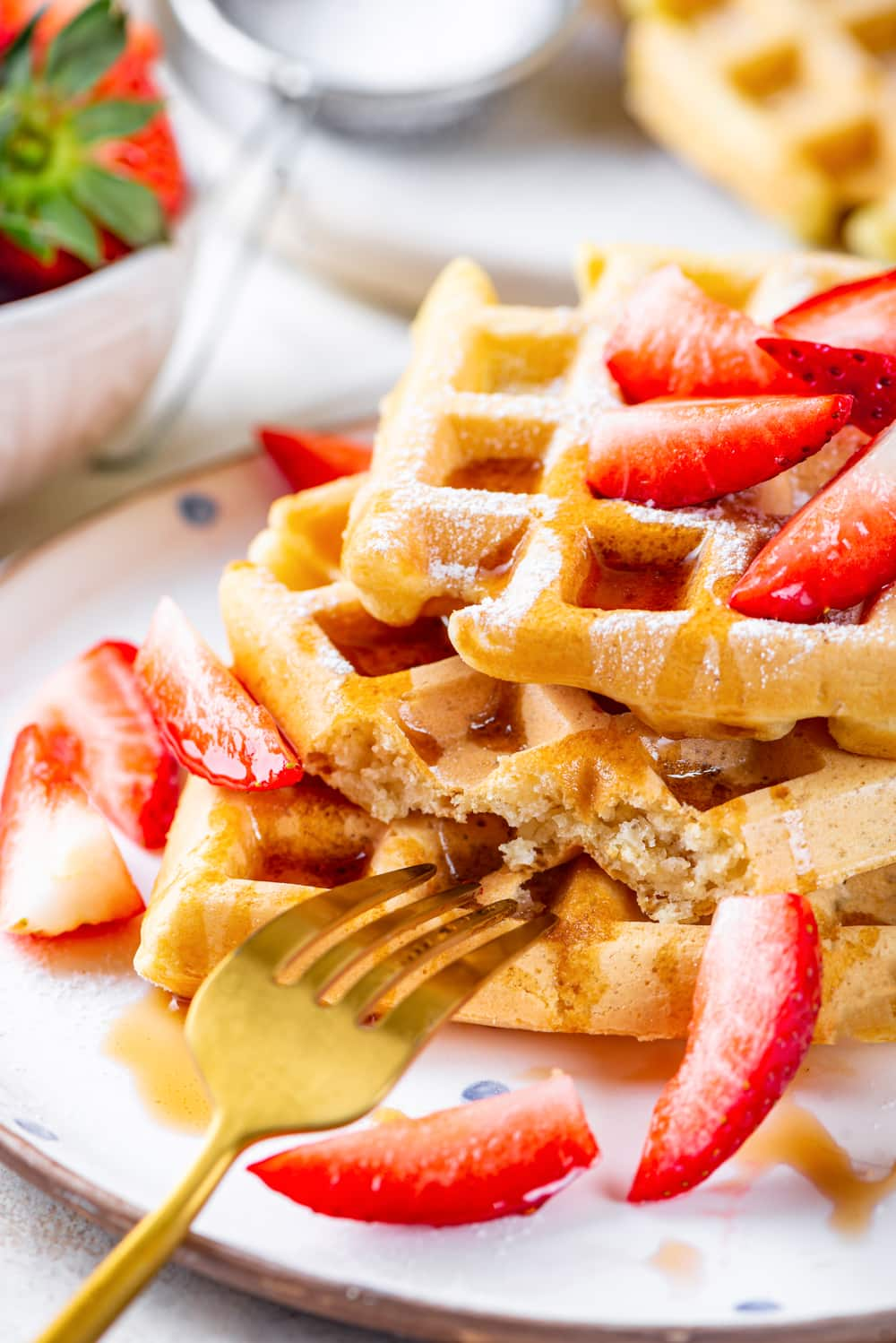 A stack of three square vegan waffles with maple syrup and cut up strawberries on them. The waffles are on a white plate and a gold fork is at the front of the plate touching the bottom waffle. There is part of bowl and strawberries and waffle in the background behind the plate.