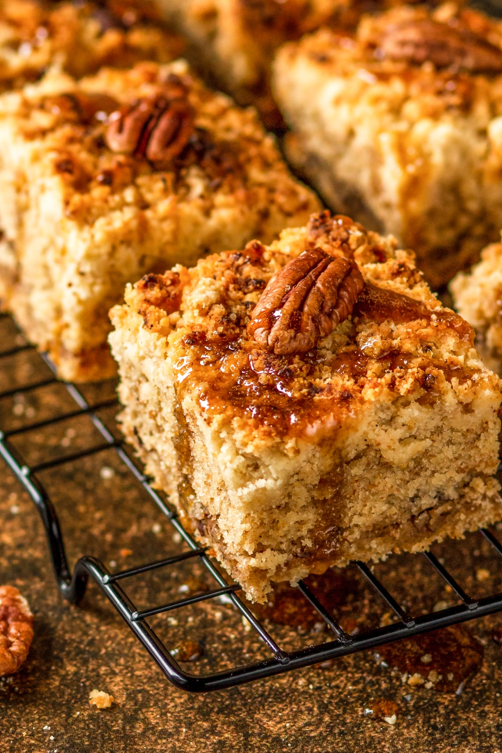 A close up view of a piece of coffee cake with multiple pieces of coffee cake behind it. Each piece of coffee cake has one pecan on top and they are sitting on a wire rack.