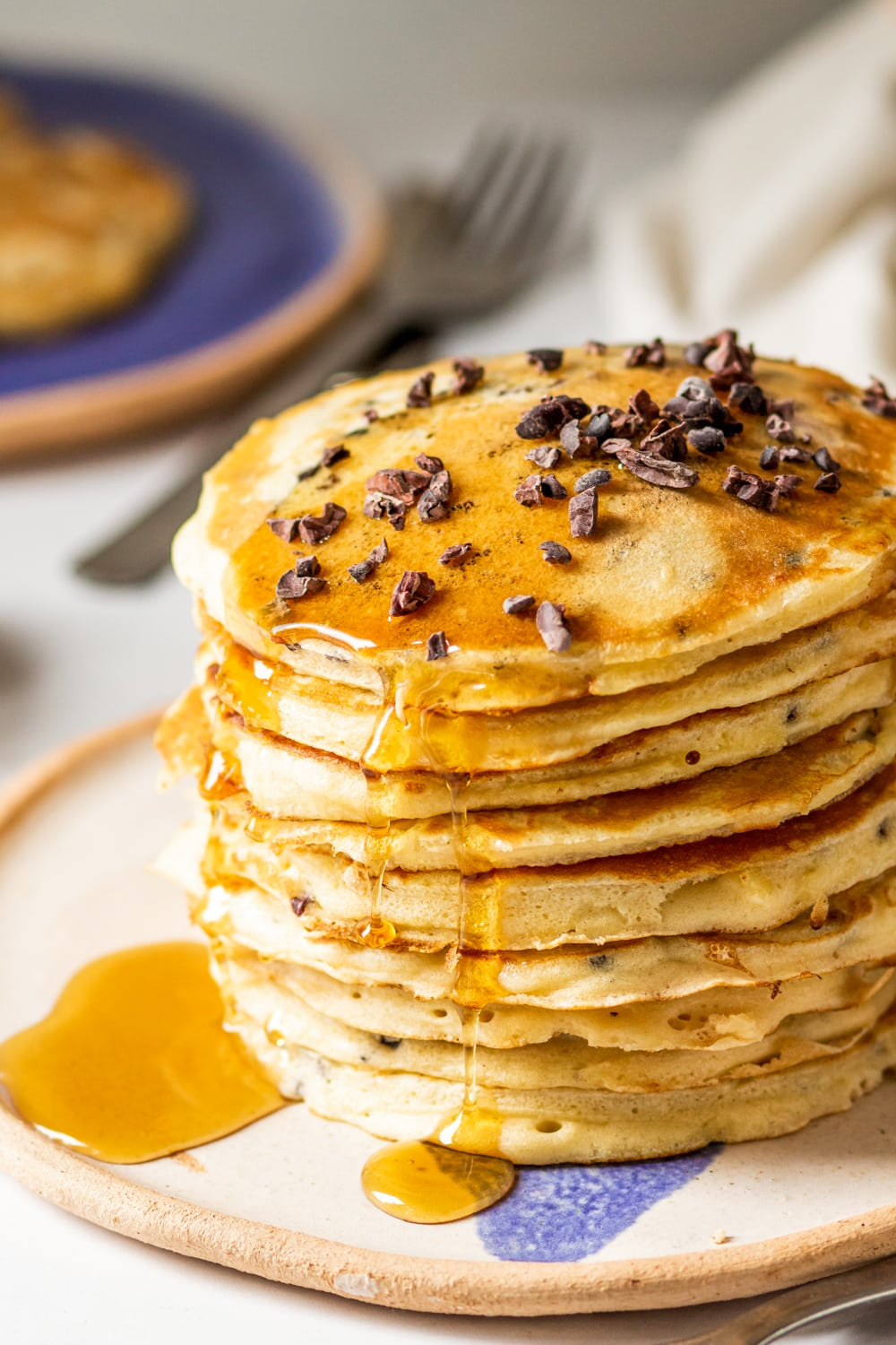 A stack of nine chocolate chip pancakes on a white plate. Syrup is dripping down the side of the pancakes with a small pool of syrup on the plate. Chocolate chips are on scattered on the surface of the top pancake.