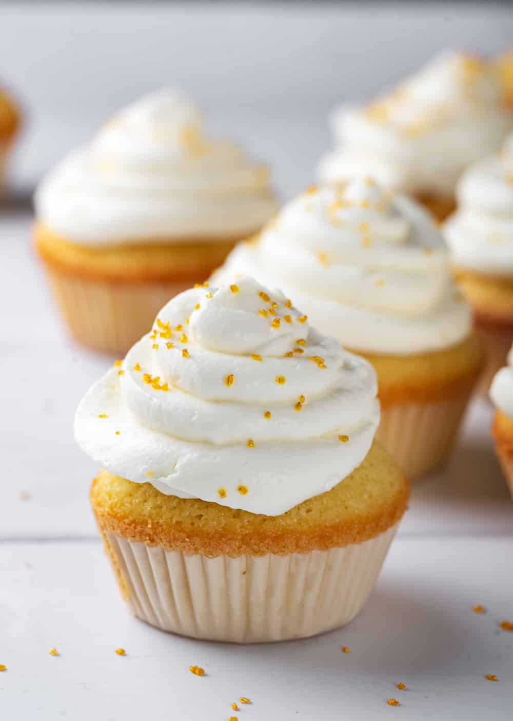 A keto vanilla cupcake with cream cheese frosting on a white counter. There are several cupcakes set behind the front cupcake.