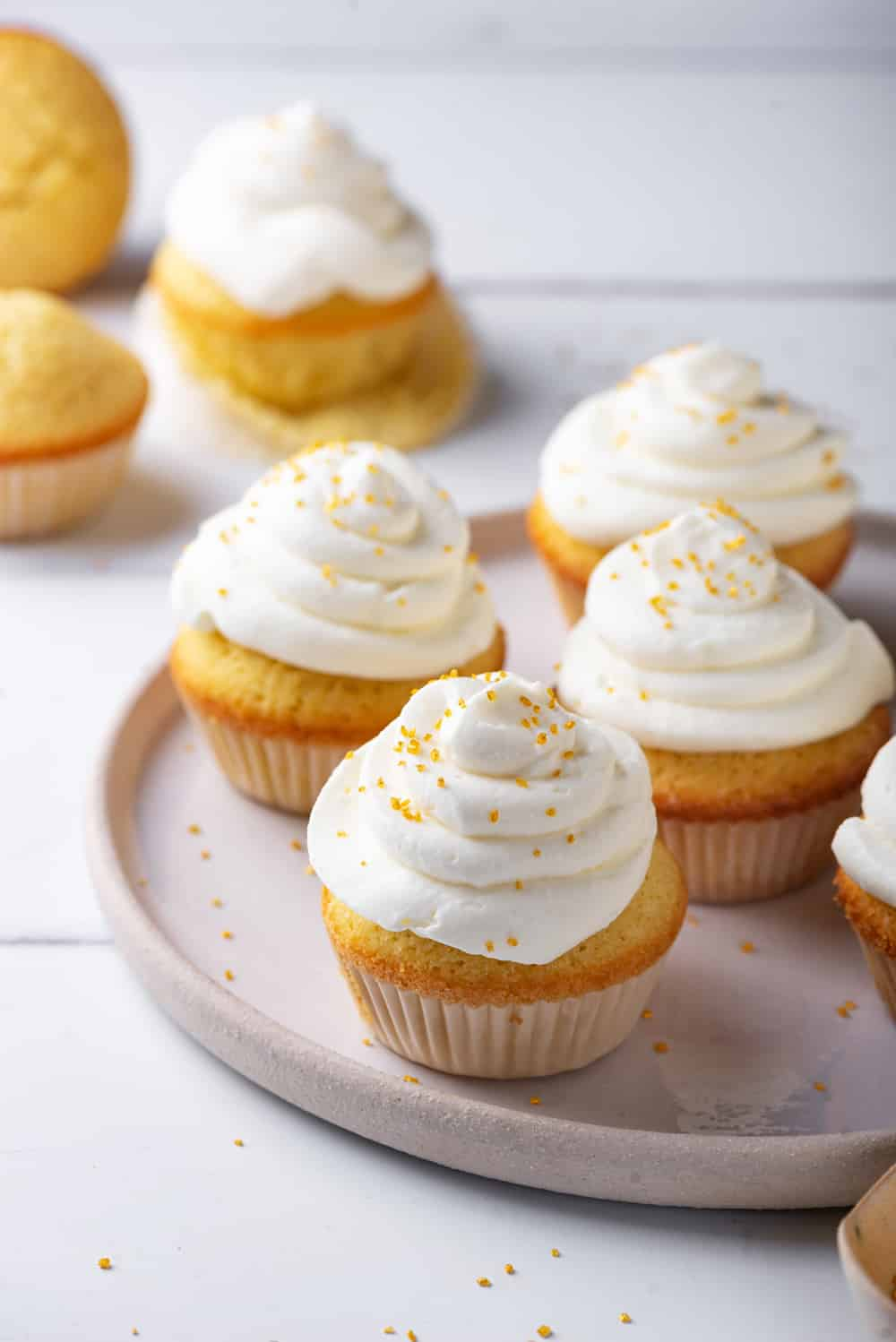 A grey plate with four keto vanilla cupcakes with keto cream cheese frosting on top. There is one frosted cupcake with the wrapping off behind the plate on the white counter. Two unfrosted cupcakes are next to it with one standing up and one on its front side.