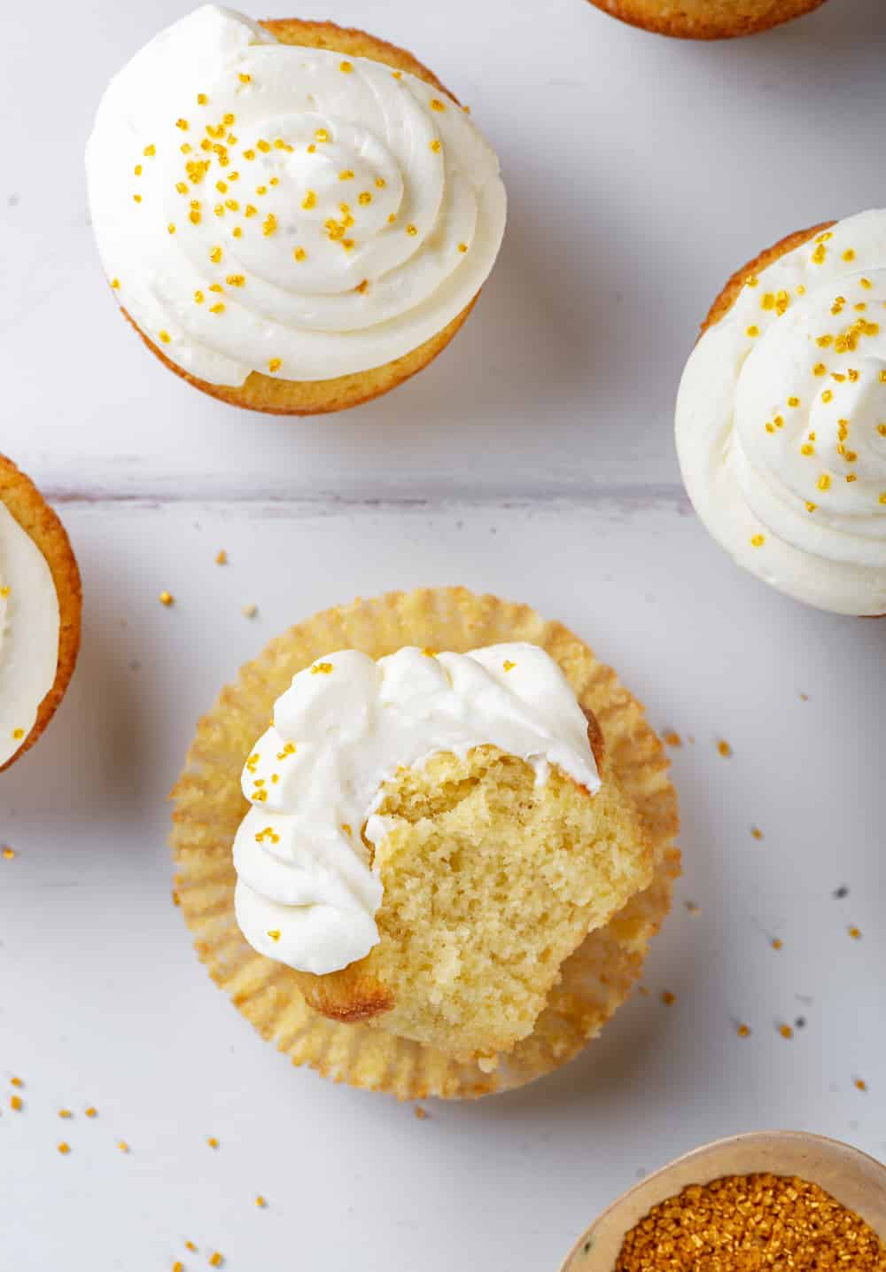 An overhead view of a keto vanilla cupcake with keto cream cheese frosting on it. The cupcake is on its back with a bite taken out of it with the inside of the cupcake facing up. There are two frosted cupcakes standing upright behind the cupcake . All the cupcakes are on a white counter.