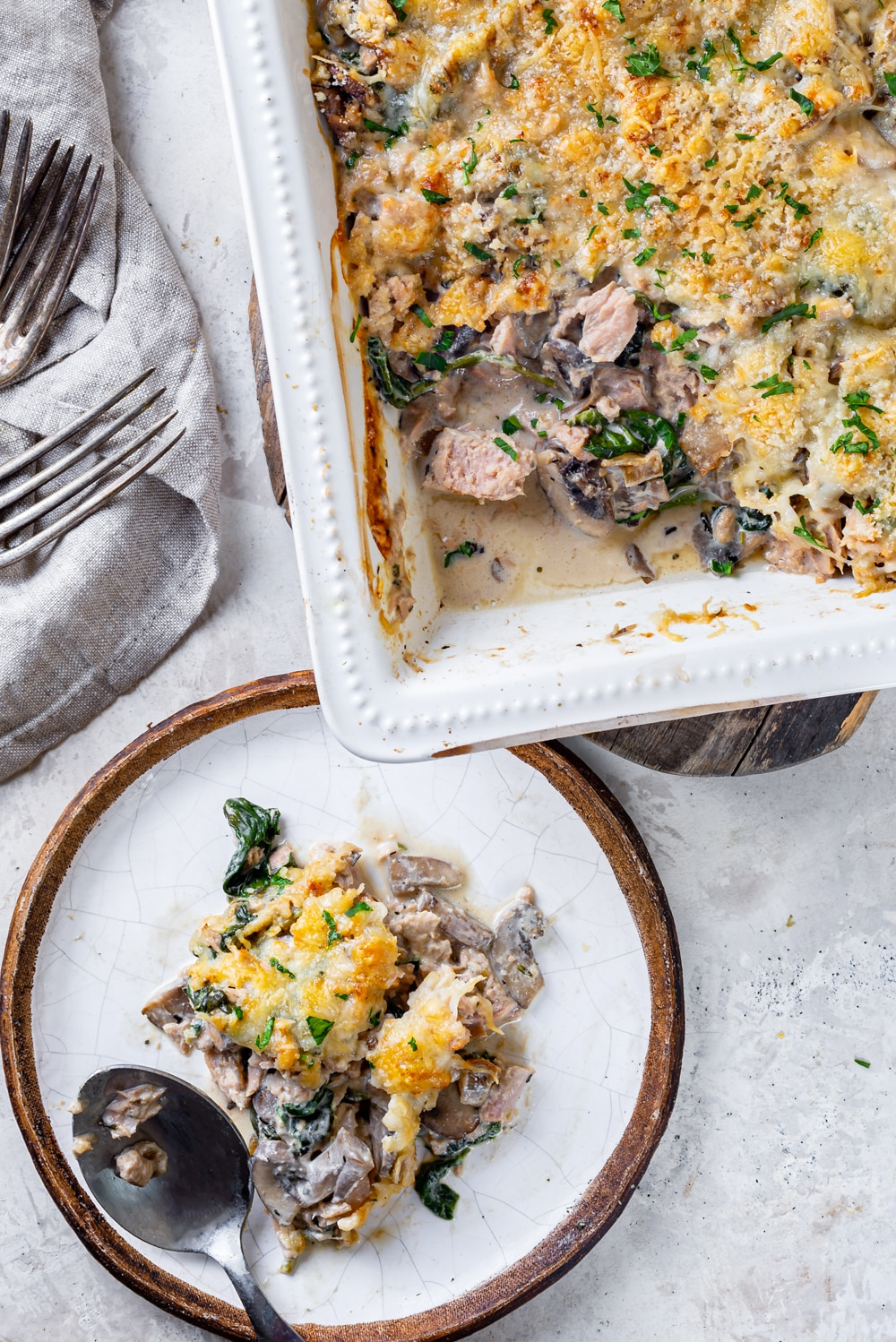An overhead view of a white plate with keto tuna casserole on it with a metal spoon on the front edge of the plate. A casserole dish filled with the keto tuna casserole is directly behind the plate slightly off to the right. The plate is on a white counter and the casserole dish is on a wooden board on the counter