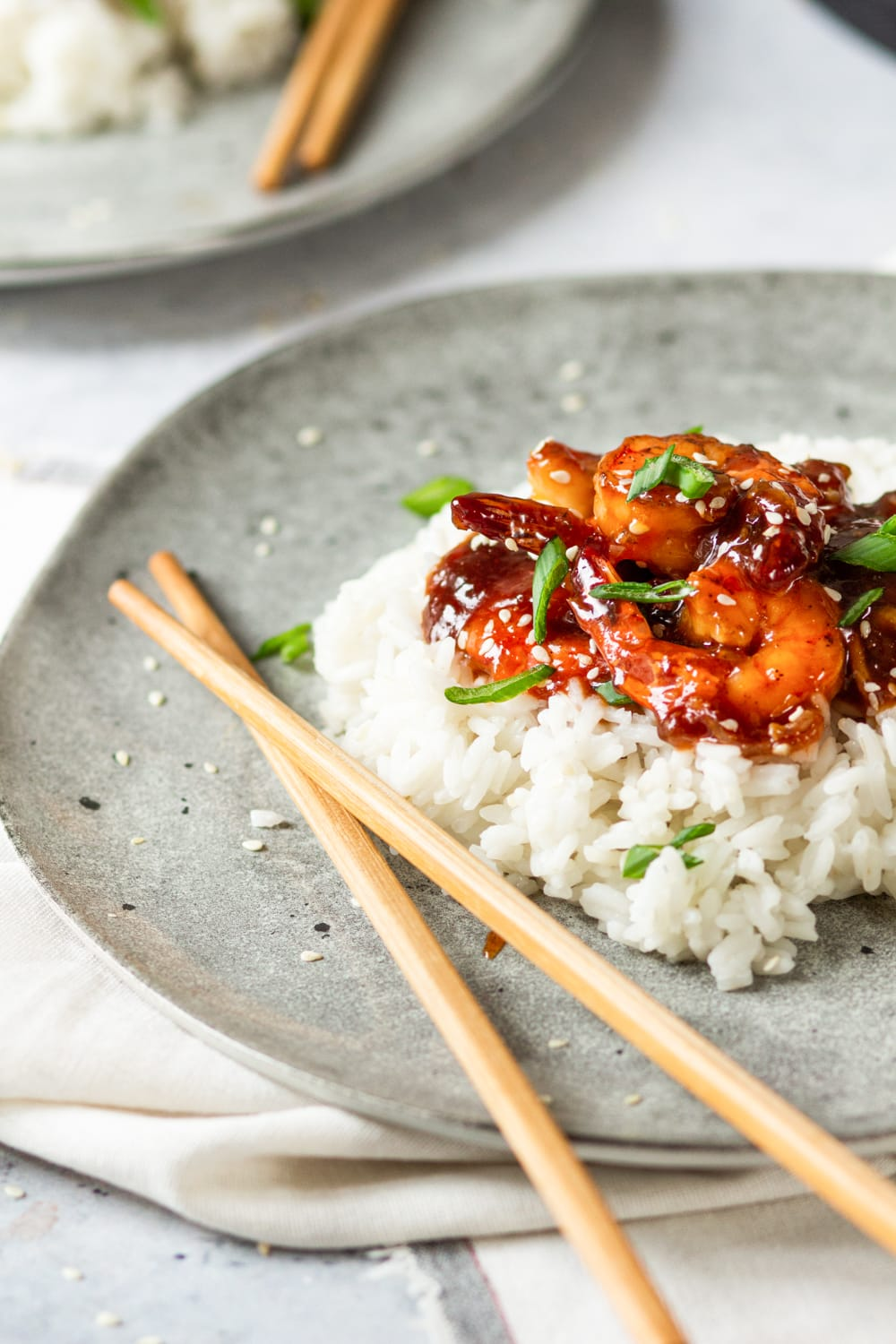 A few pieces of sweet and sour shrimp on a bed of white rice on a grey plate. There is a set of chopsticks crossed over one another to the left of the rice. The plate is on a white tablecloth.