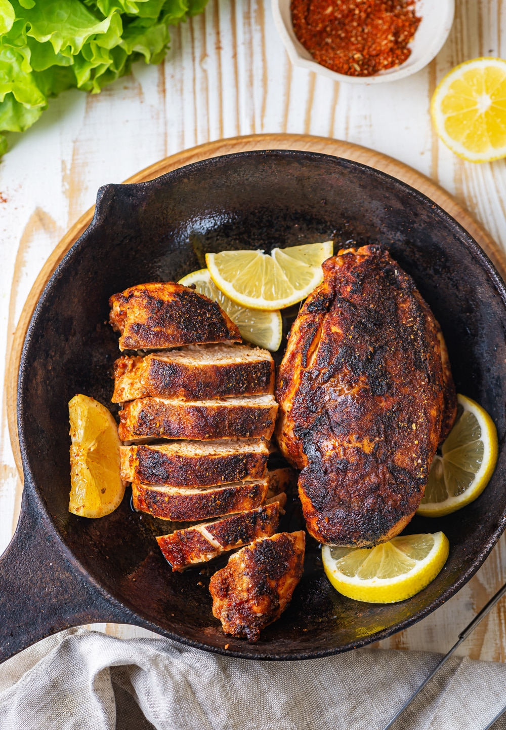 An overhead view of a whole cooked piece of blackened chicken and a sliced cooked piece of blackened chicken in a skillet. Five lemon slices are surrounding the chicken in the skillet. The skillet is on a wooden saucer on a wood table.