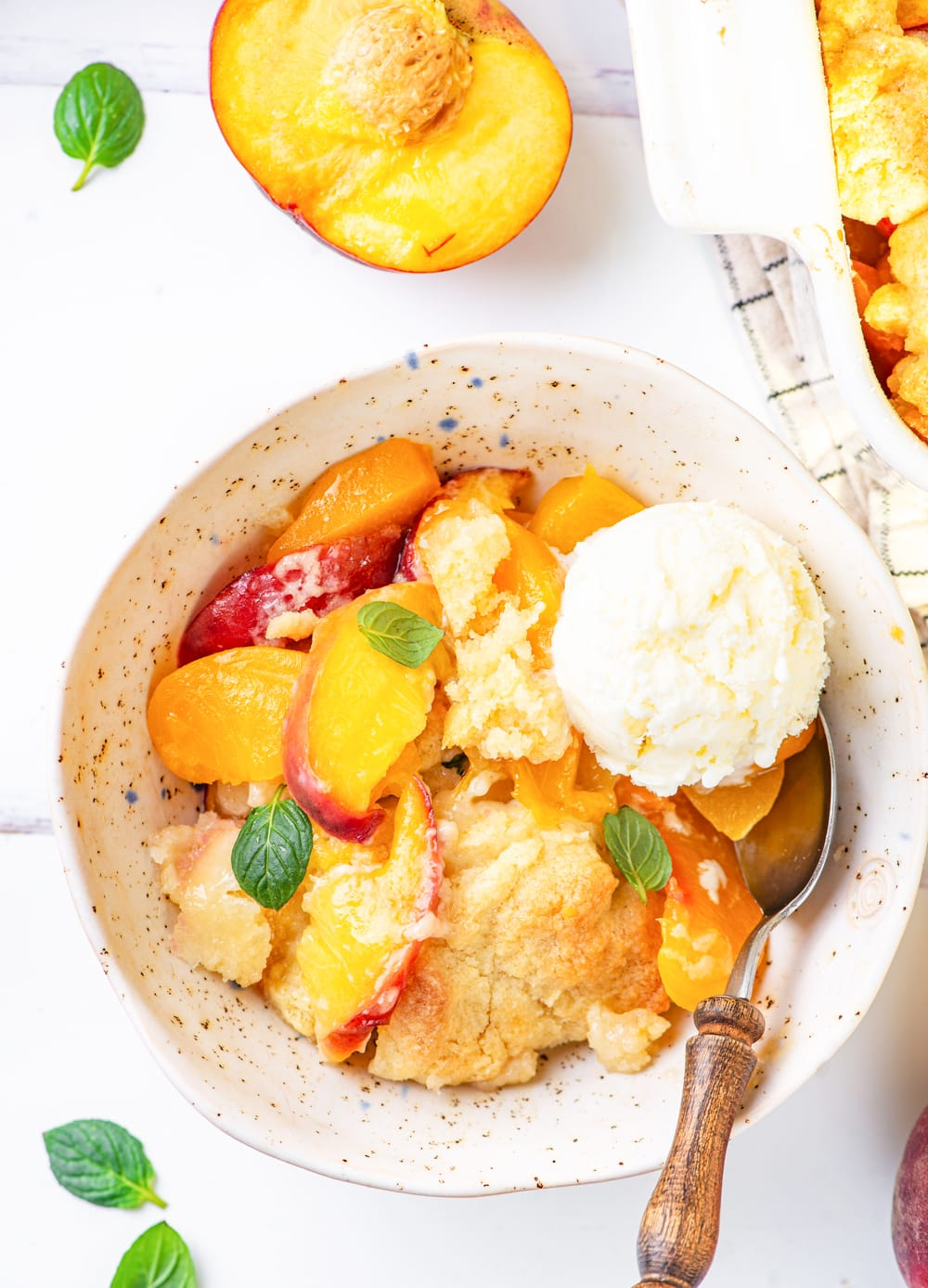 A white bowl filled with vegan peach cobbler and a scoop of vegan vanilla ice cream. A metal spoon is at the front of the bowl. with the head of the spoon just below the scoop of ice cream. There is half a peach with the inside facing up directly behind the bowl. Everything is on a white counter.