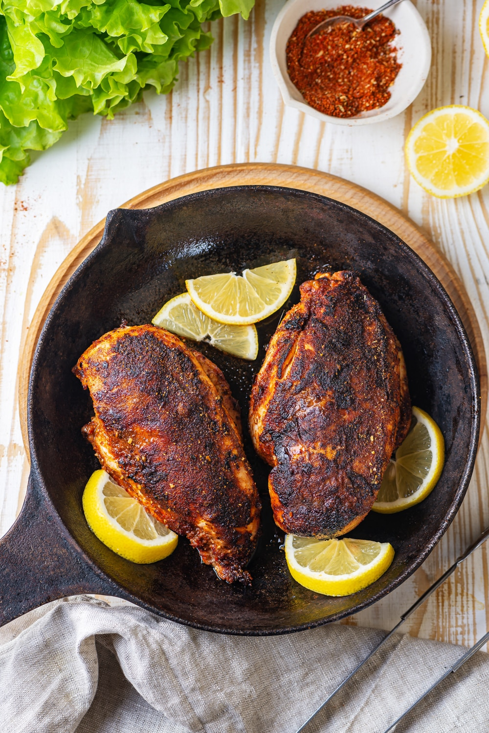 An overhead view of two whole pieces of cooked blackened chicken in a skillet. Five lemon slices are surrounding the chicken in the skillet. The skillet is on a wooden saucer. There is a white bowl of seasonings behind the skillet and everything is on a wood table.