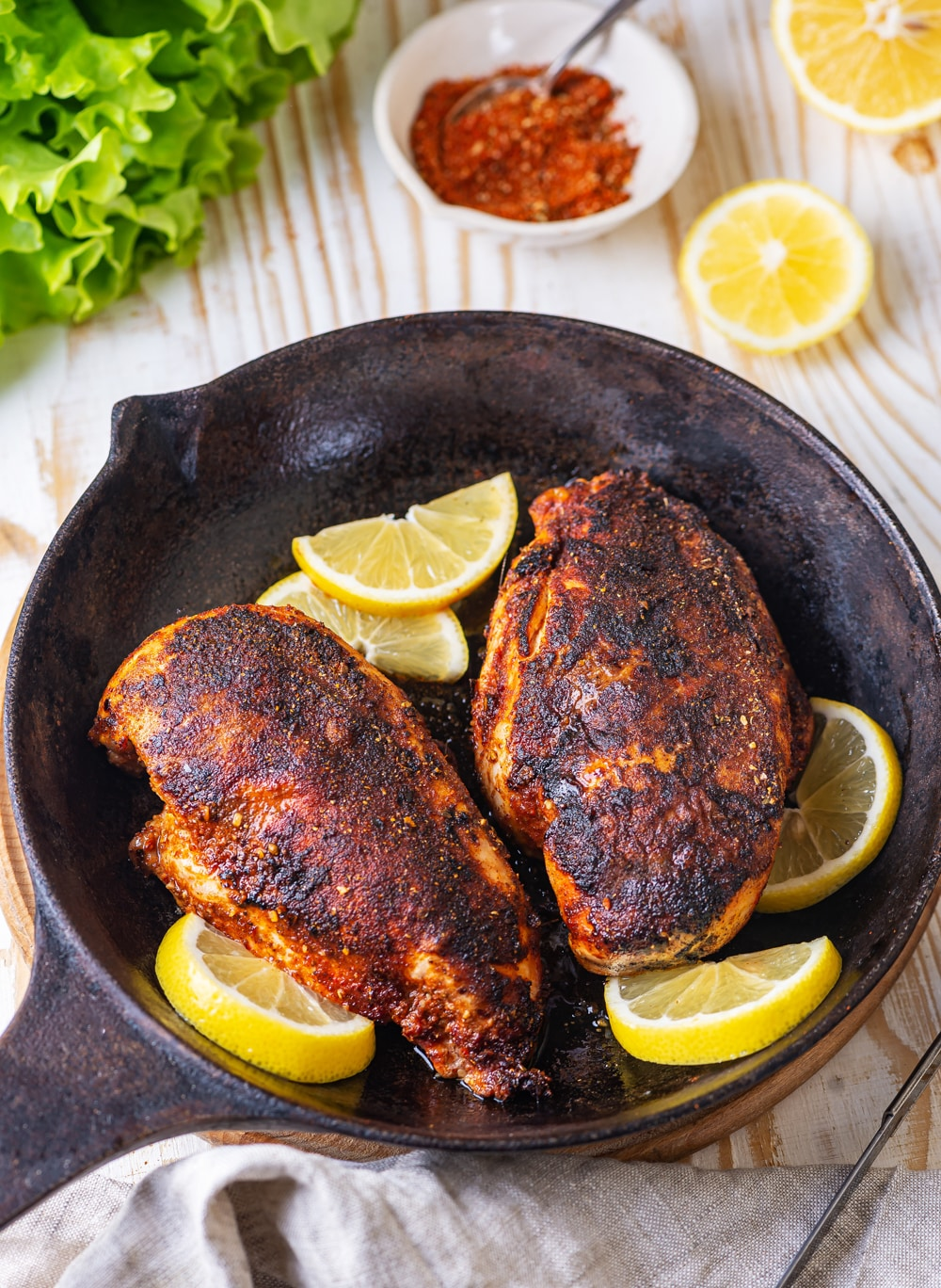 Two whole pieces of cooked blackened chicken in a skillet. Five sliced lemons are surrounding the chicken. A small white bowl of seasonings is set behind the skillet with two lemon halves next to it. Everything is on a wooden table.