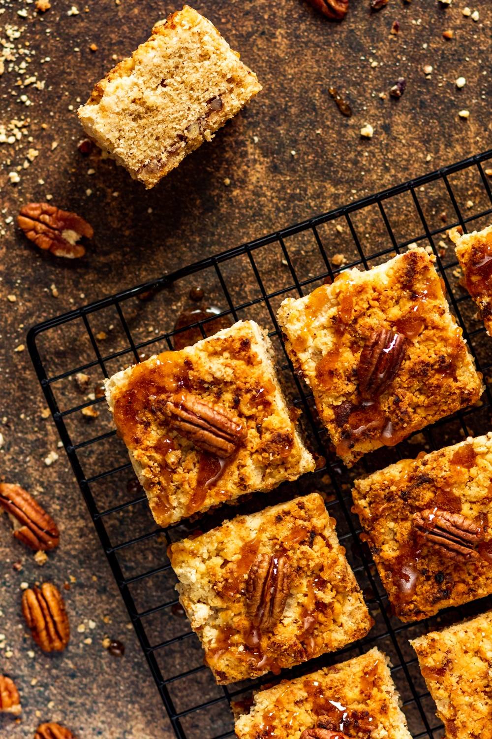 An overhead view of a couple of squares of gluten free coffee cake on a wire rack sitting on stone. There is one pecan on the top of each piece of coffee cake. One piece of coffee cake is set on its side on the stone.