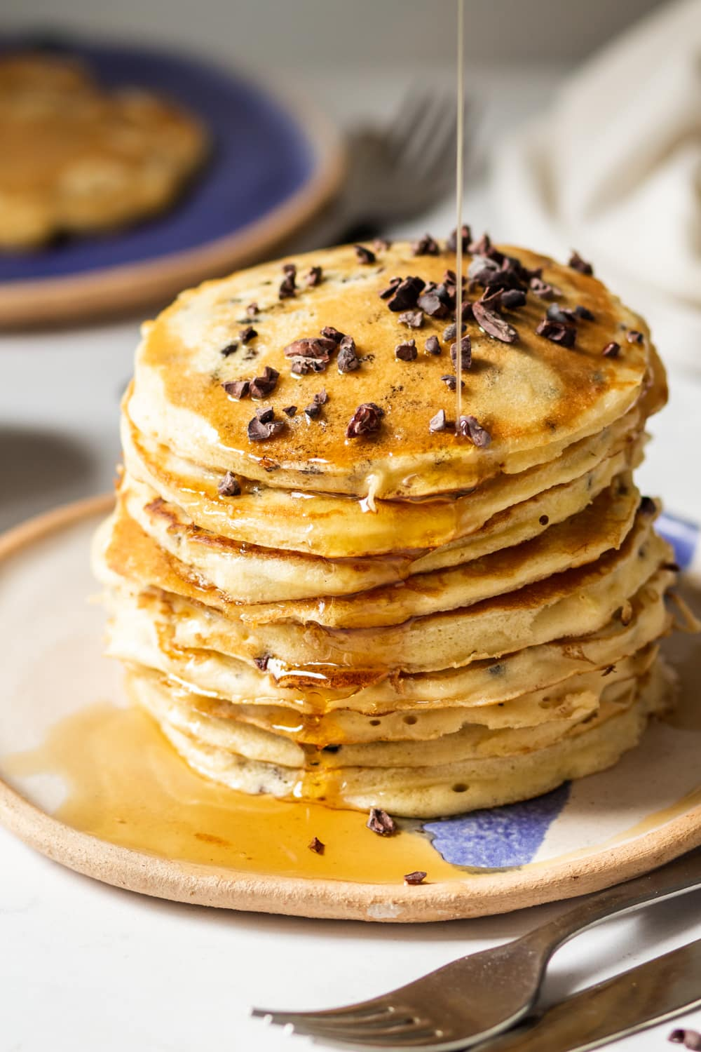 A stack of nine chocolate chip pancakes on a white plate. Syrup is being poured on the pancakes and is dripping down the side of the stack. A fork and knife are set next to the plate.