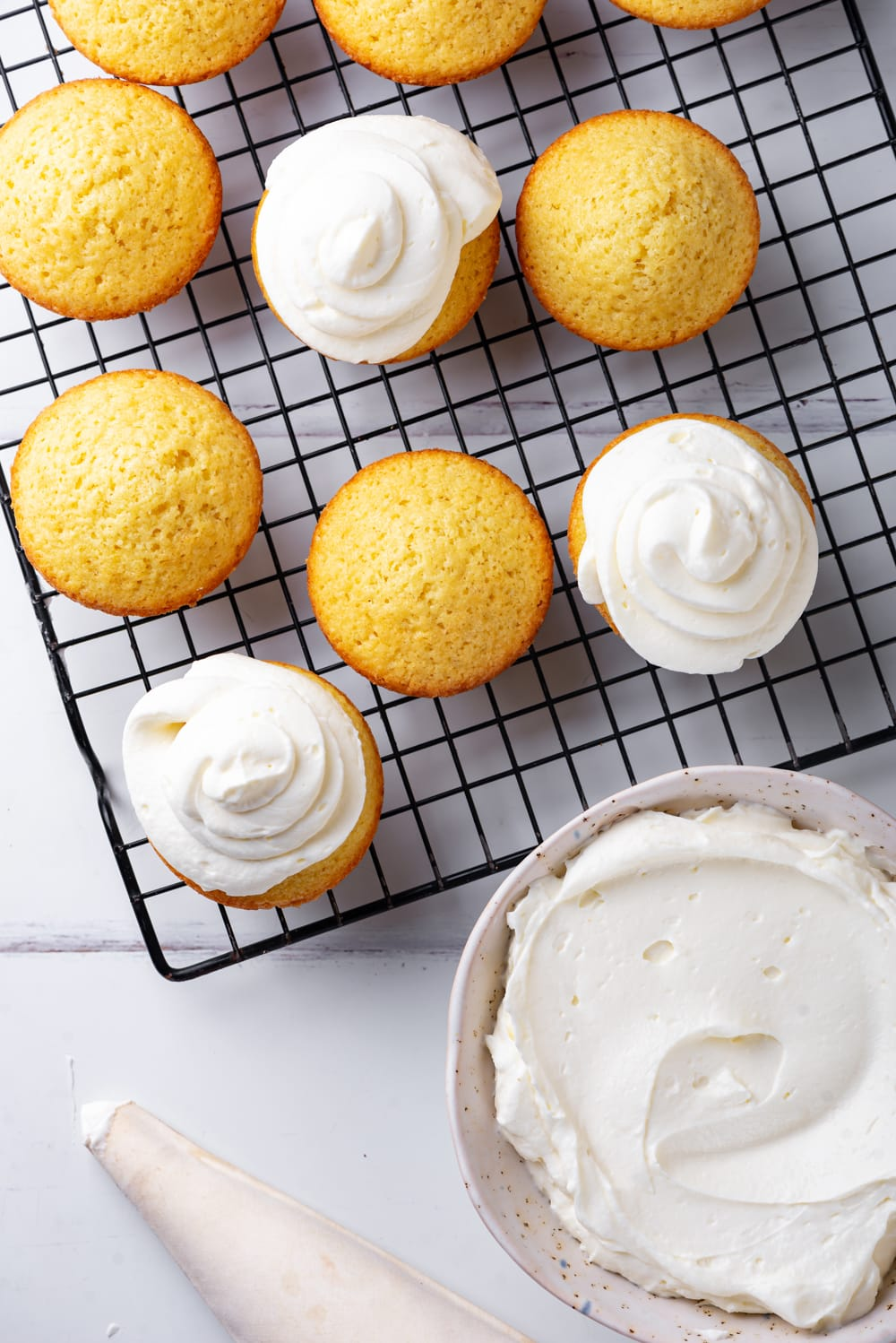 An overhead view of a bowl of keto cream cheese frosting with a frosting piper filled next to it. Behind the bowl is a black wire rack with three frosted keto vanilla cupcakes and four unfrosted. Everything is set on a white counter.
