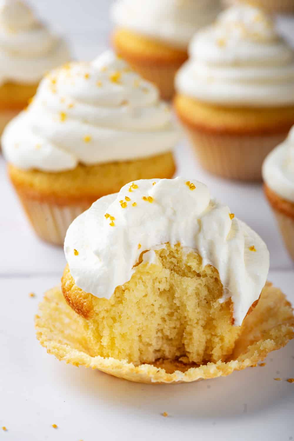 A keto cream cheese frosted vanilla cupcake with a bite taken out of the front sitting in a cupcake wrapper. There are a couple of keto cupcakes behind it and they are all on a white counter.