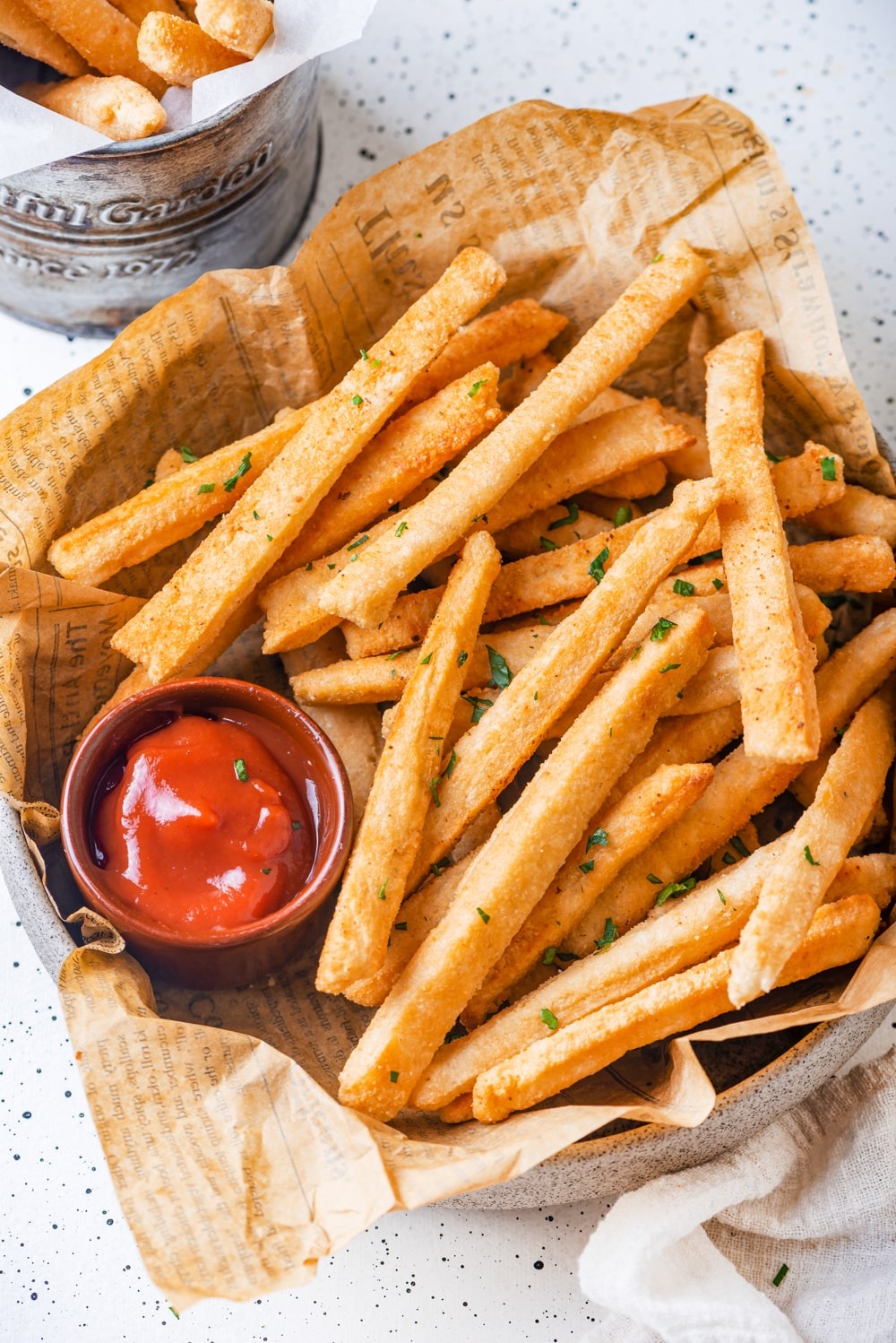 An overhead view of a basket of keto french fries. The french fries are laying on top of a sheet of brown newspaper. A small cup of ketchup is on the left side of the fries in the basket. The basket is on a white counter.