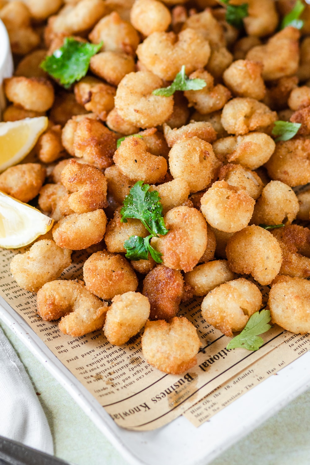 Popcorn shrimp on top of brown newspaper on a white square plate with the corner of the plate showing.