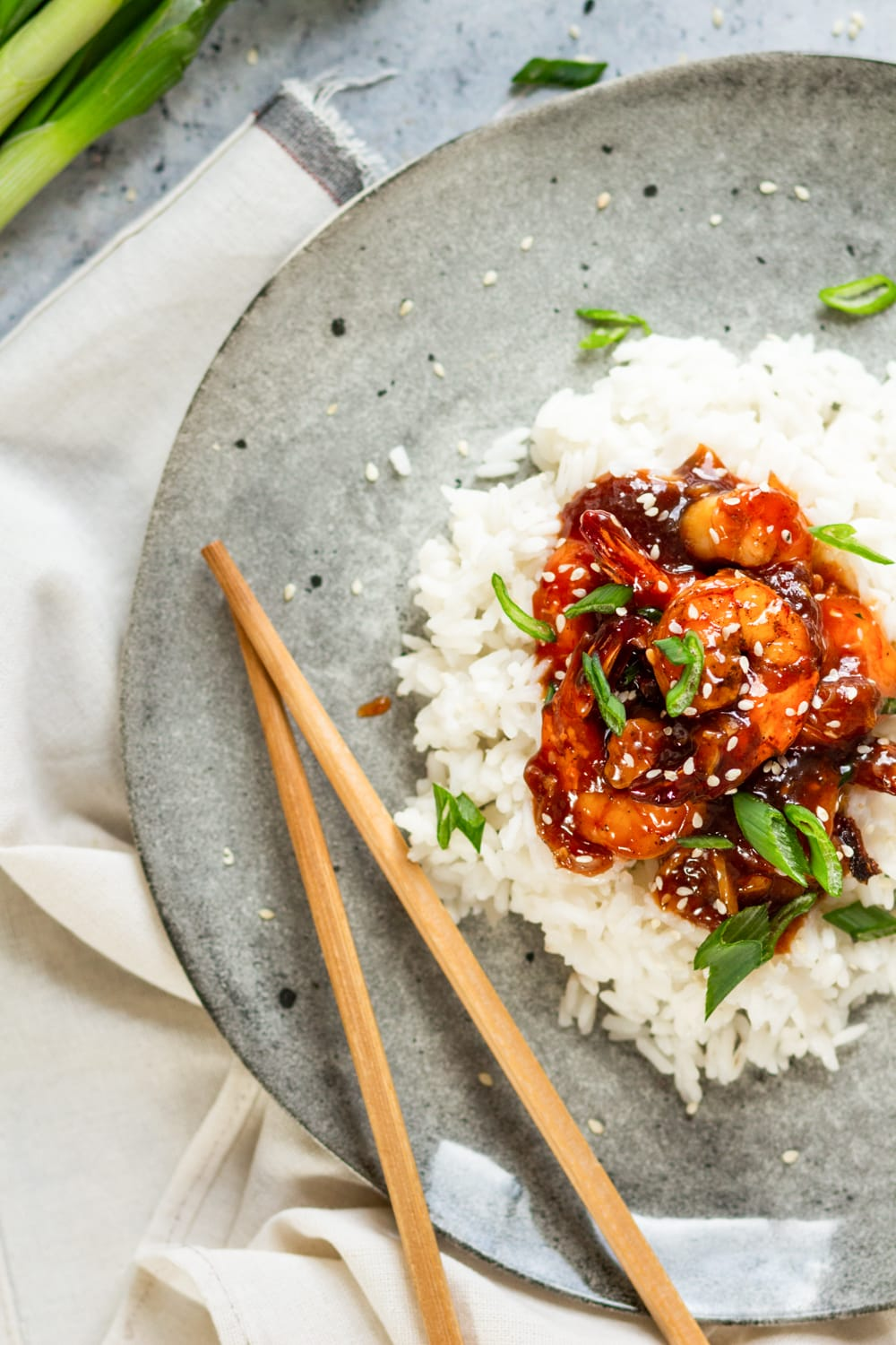 An overhead view of a few pieces of sweet and sour shrimp on a pile of white rice on a grey plate. There are sesame seeds and sliced green onions on the shrimp. A pair of chopsticks is on the plate next to the left of the shrimp. The plate is on a bunched white tablecloth.