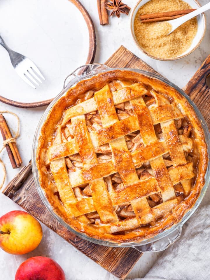 An overhead view of a vegan apple pie in a glass pie dish on a wooden cutting board. There are two apple in front of and to the left of the cutting board. A white plate with a fork on it and a white bowl filled with sugar is behind the cutting board. All of this is on a grey cutting board.