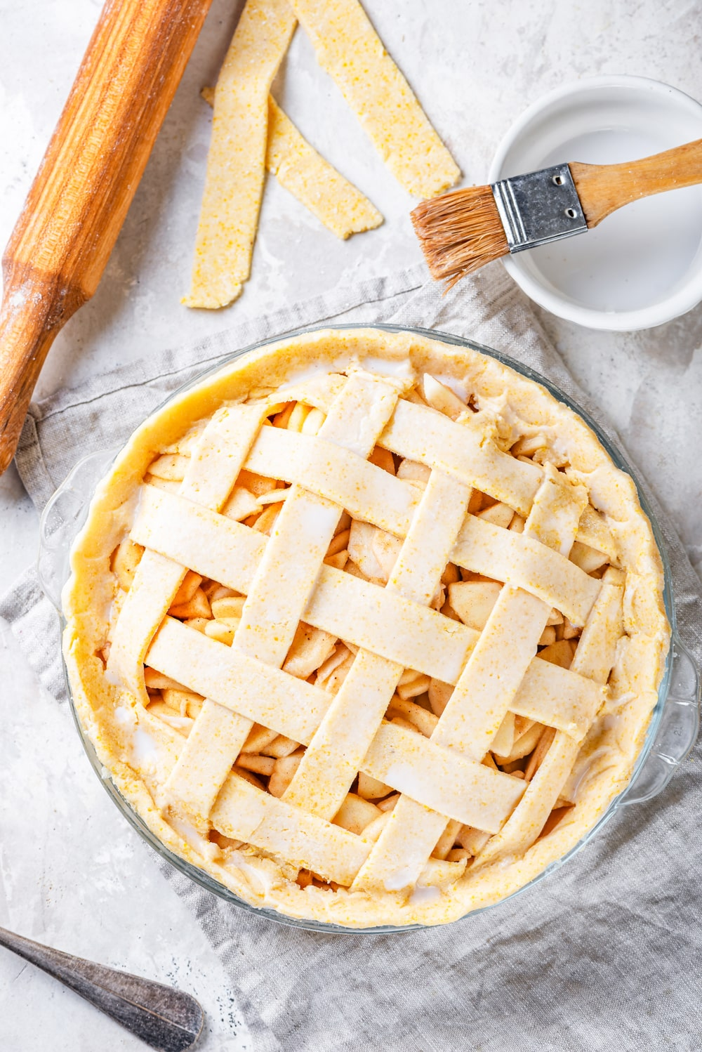 An overhead view of an uncooked vegan apple pie in a glass pie dish on a grey tablecloth. A rolling pin is behind the pie to the left and a brush on top of a small white bowl is to the right. All of these things are on a grey counter.